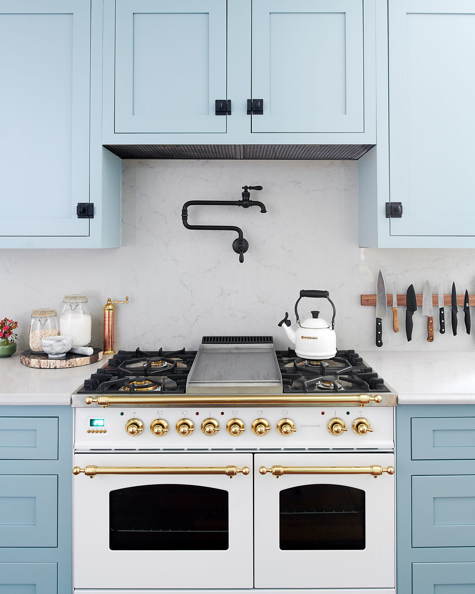 powder blue kitchen with view of stove featuring gold accents