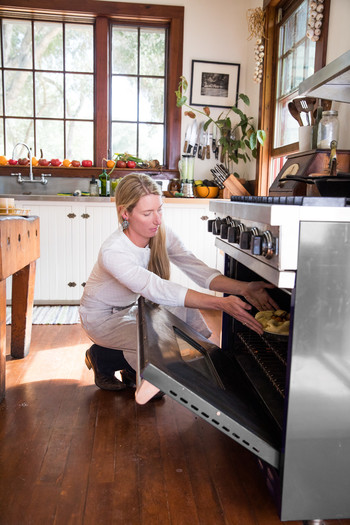 woman putting food in the oven
