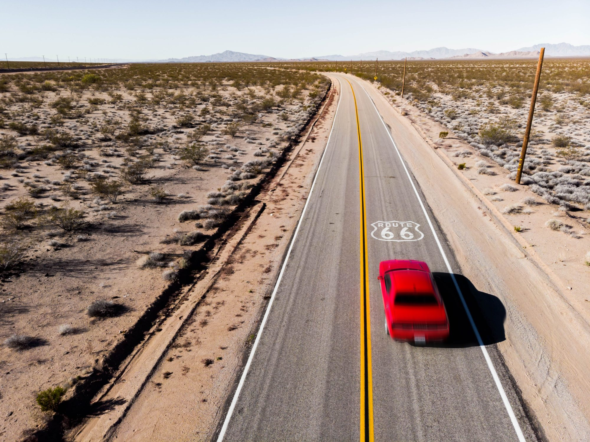 drone view of American car driving in a straight road of the famous Route 66
