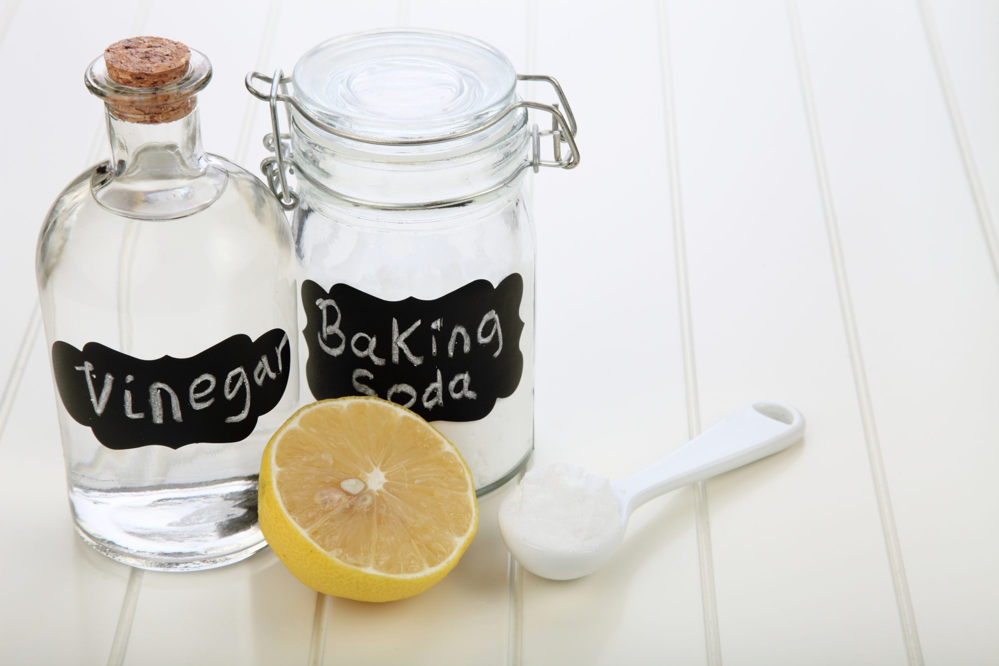 vinegar and baking soda next to lemon and measuring spoon