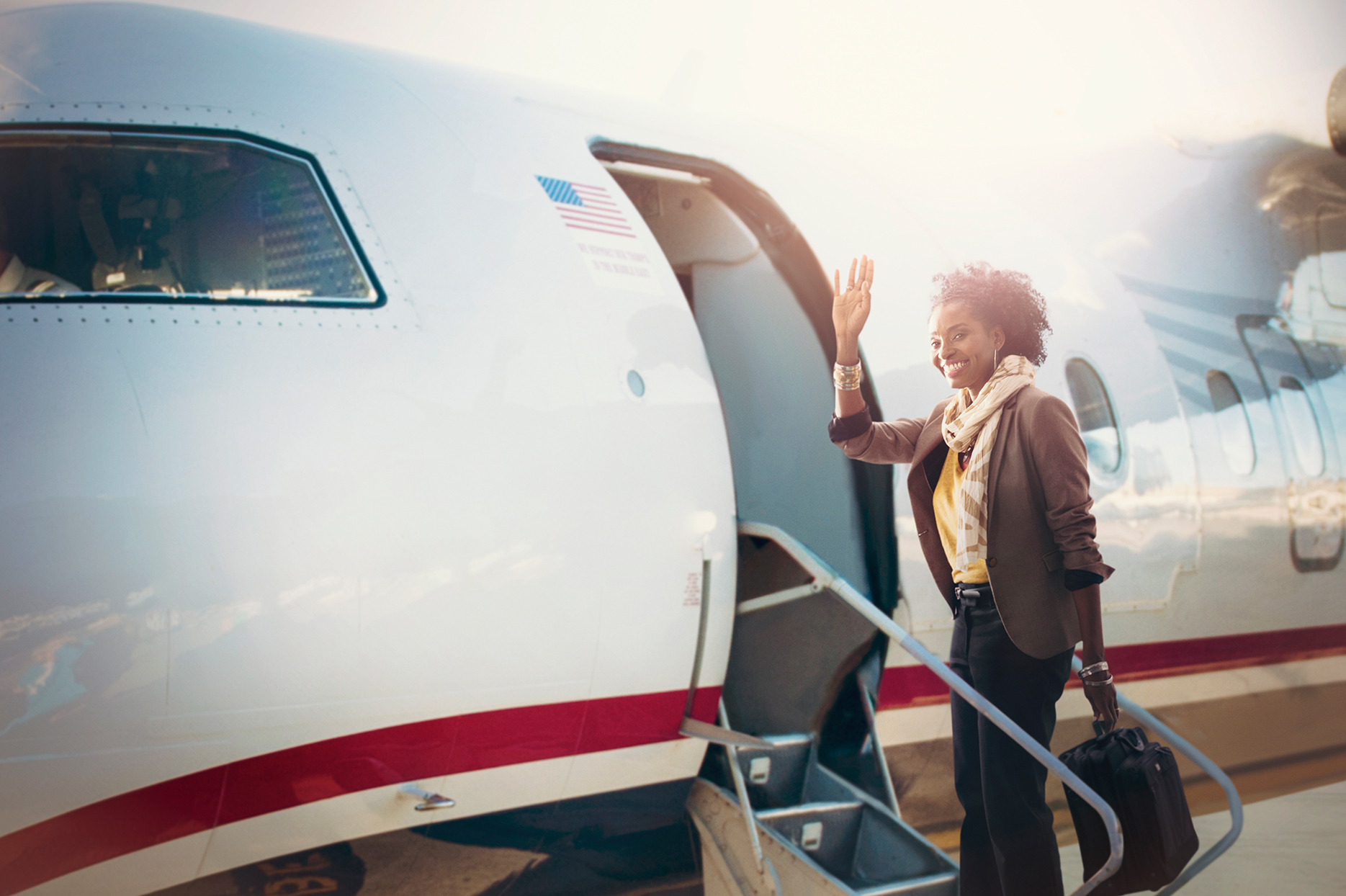 Woman waving as she boards small plane