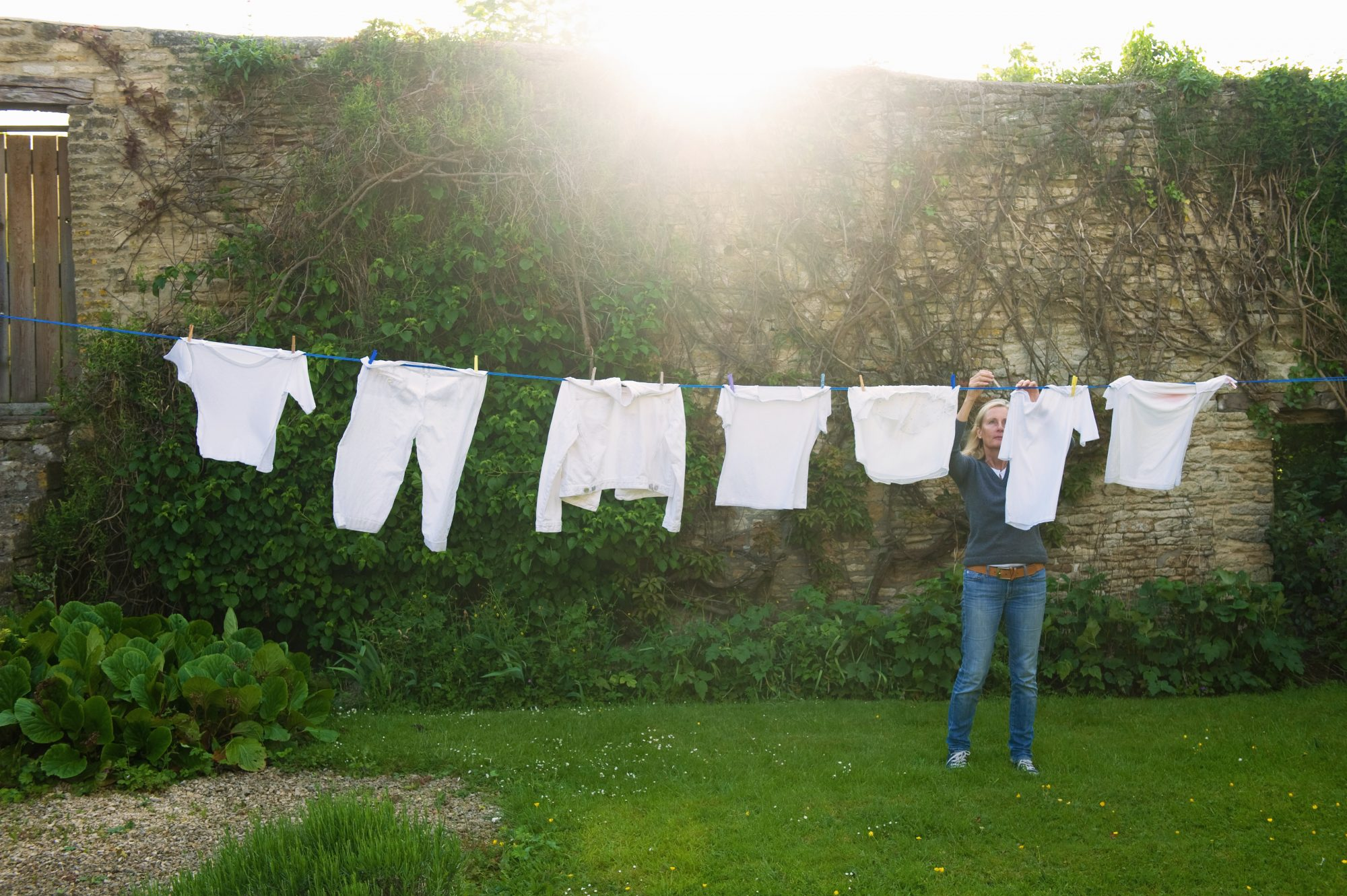 woman hanging up laundry on washing line outside