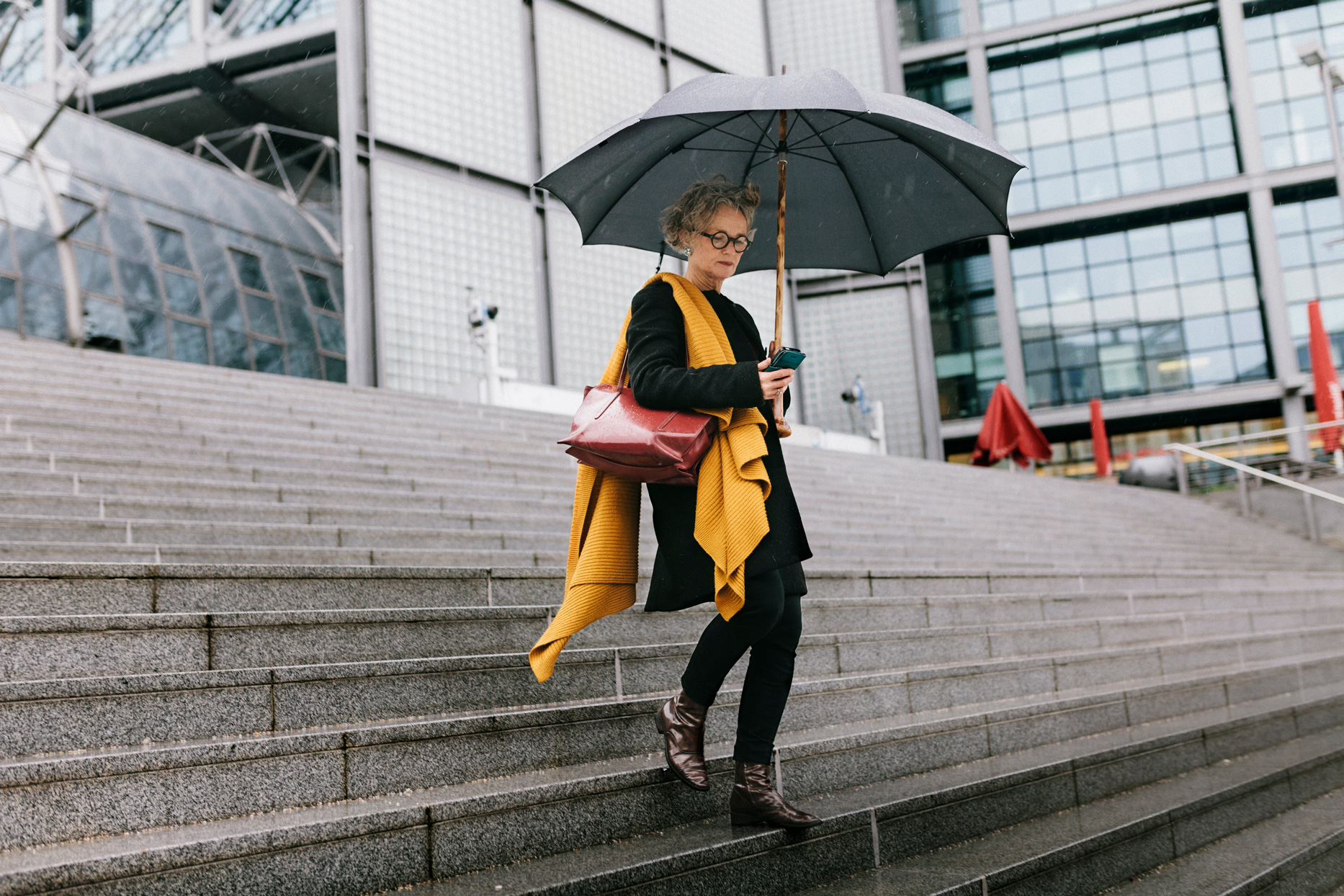 woman holding umbrella walking down steps outside of building