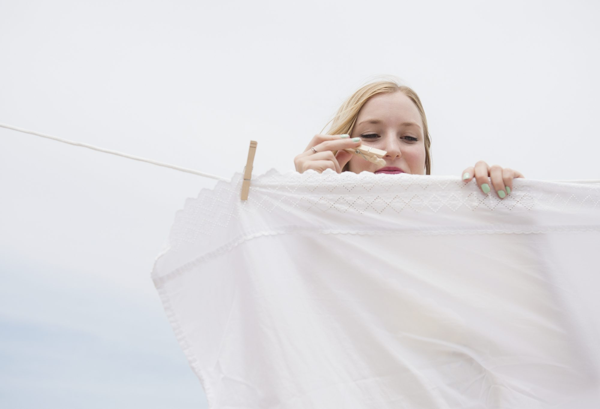 woman pinning laundry on clothing wire outdoors