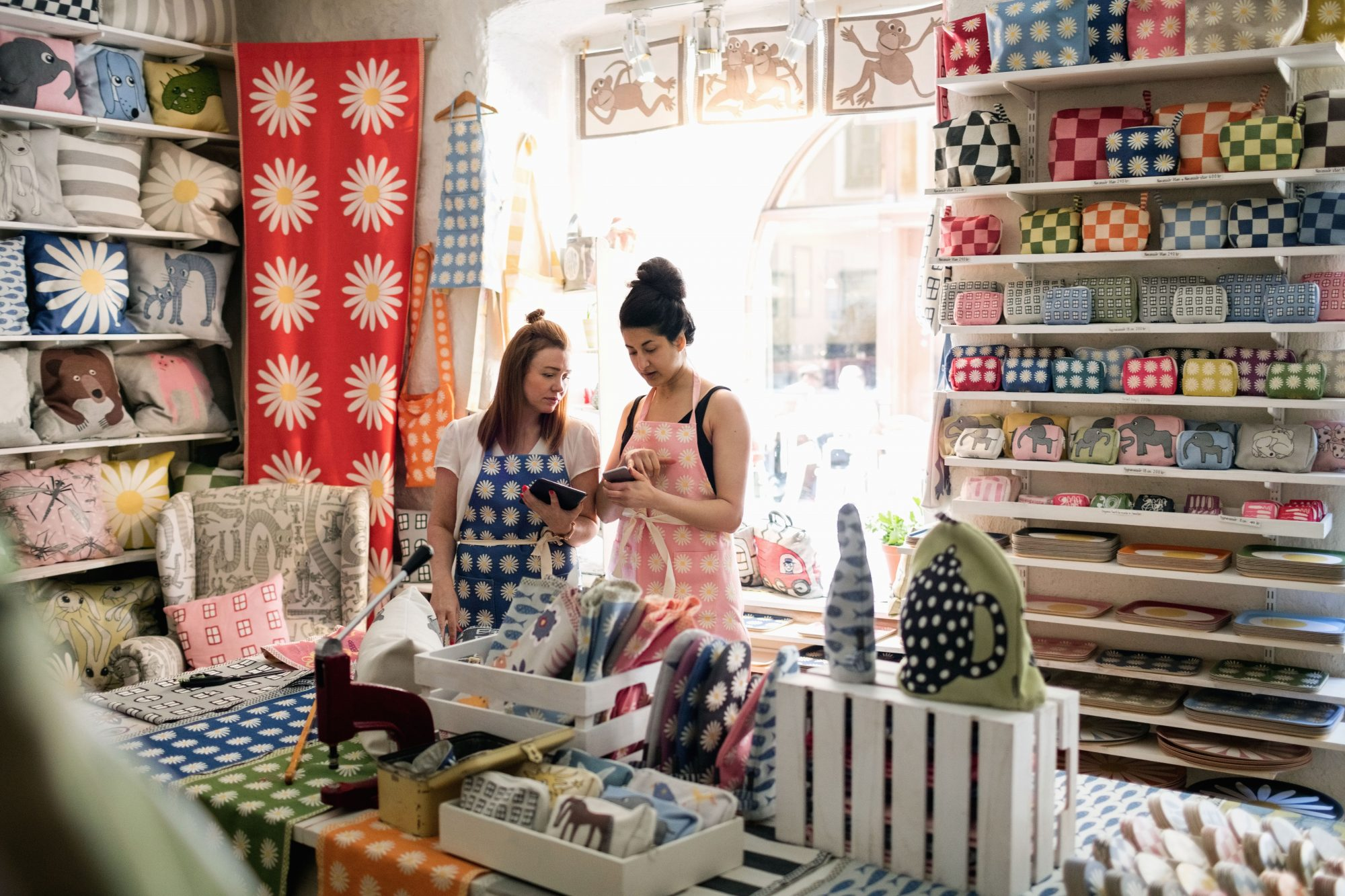 Female owners using smart phone and digital tablet while standing in fabric shop