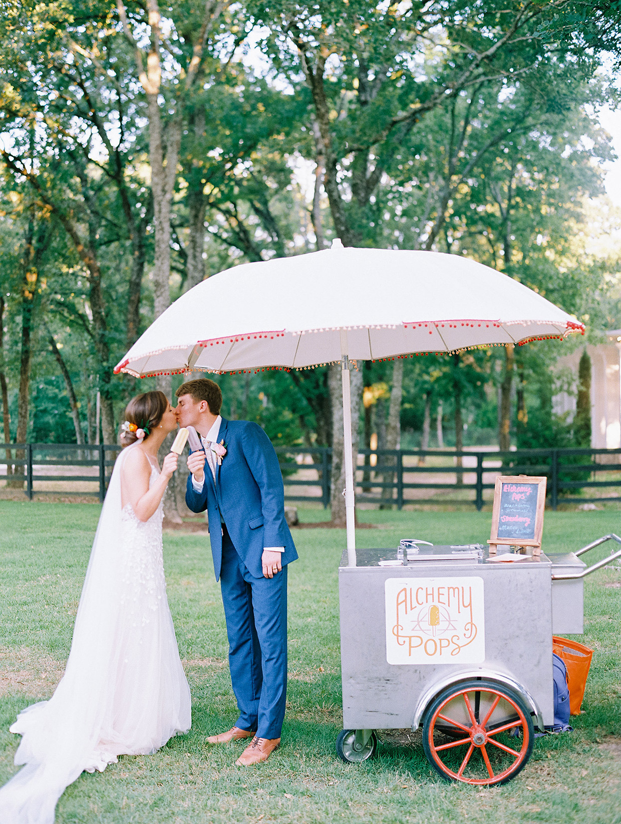 evie joe wedding couple kissing by popsicle stand