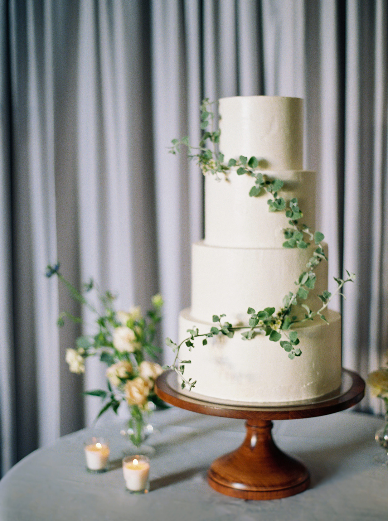 kimmie mike simple white wedding cake on wooden stand with green vine