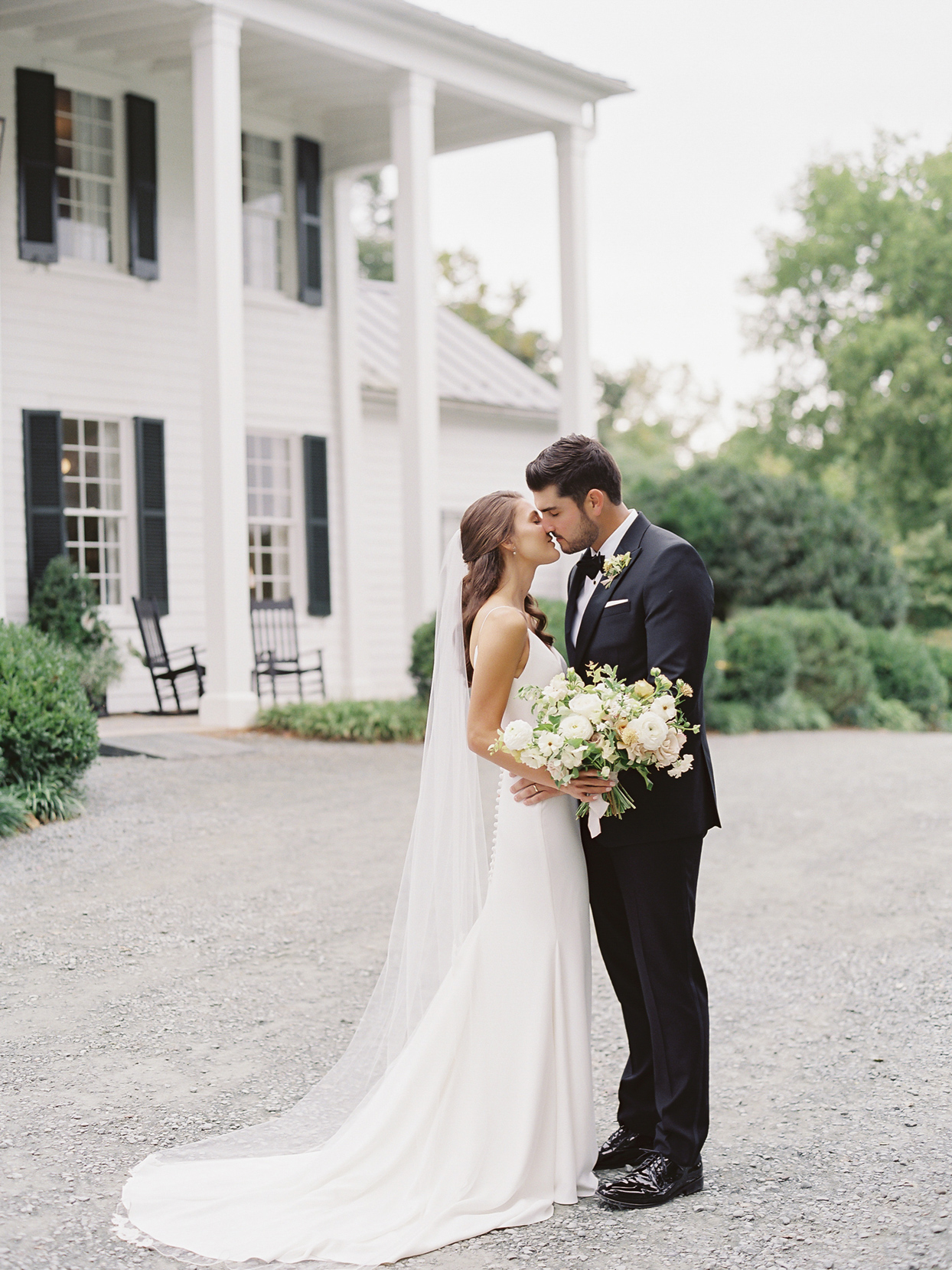 Bride and groom kissing in front of white house