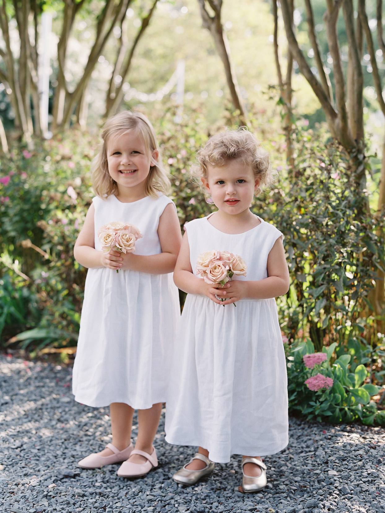 Flower girls wearing white linen dresses and carrying nosegays of roses