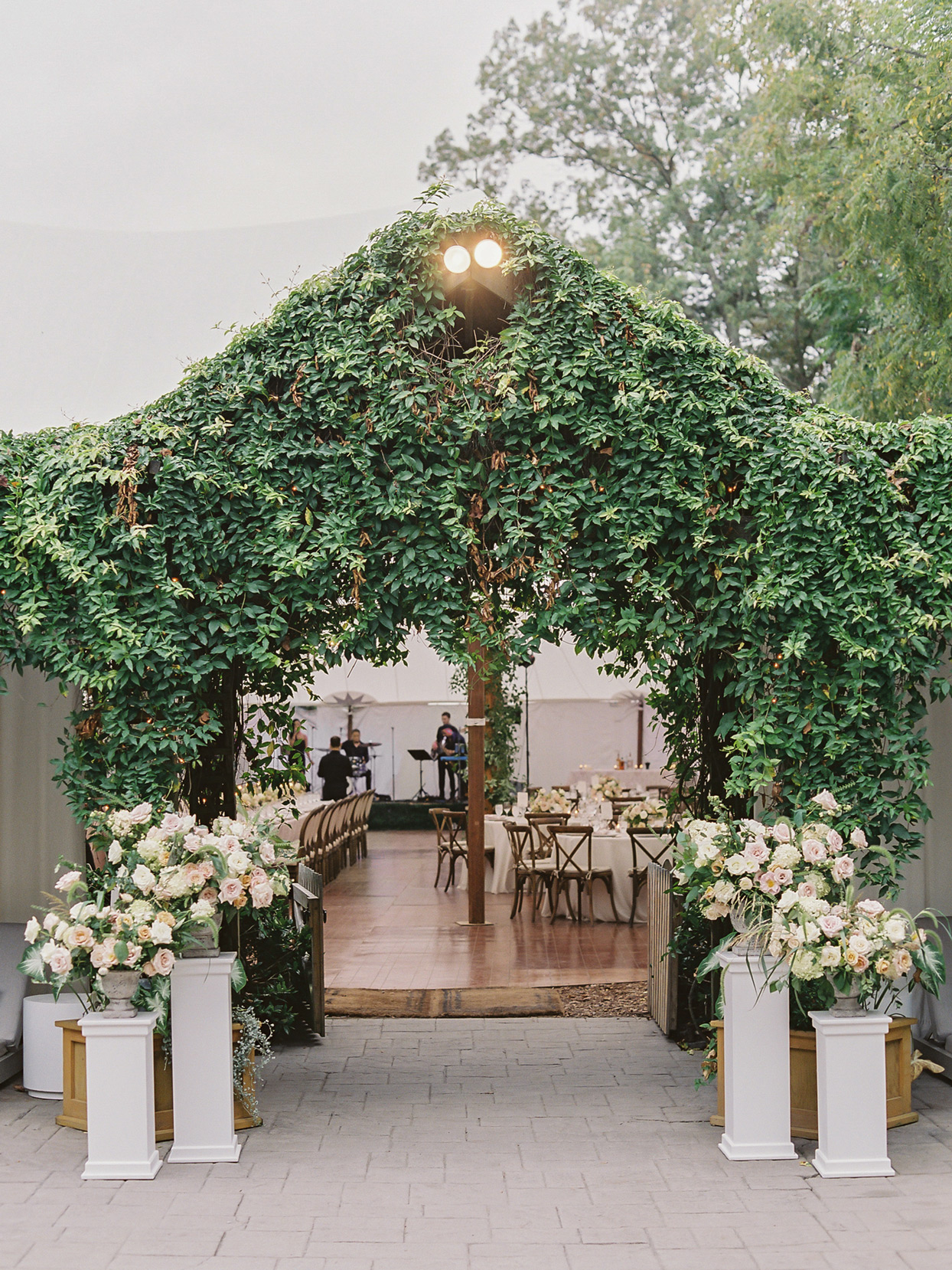 Wedding tent entrance covered in greenery