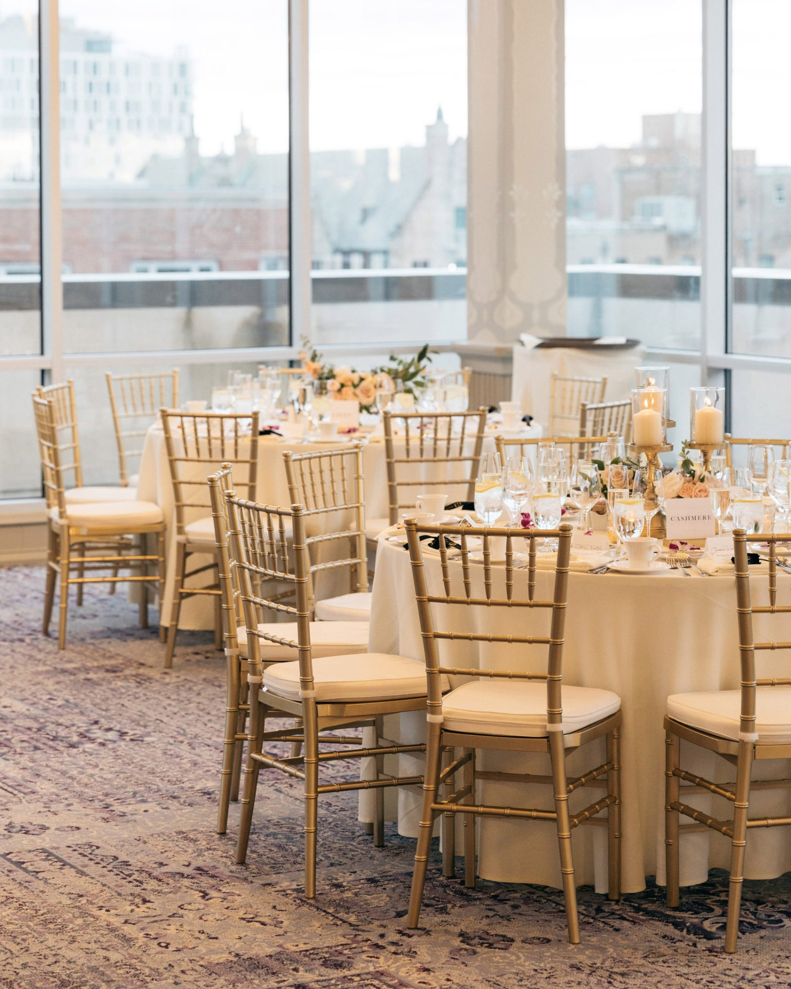 reception tables in corner floor to ceiling windows showing city