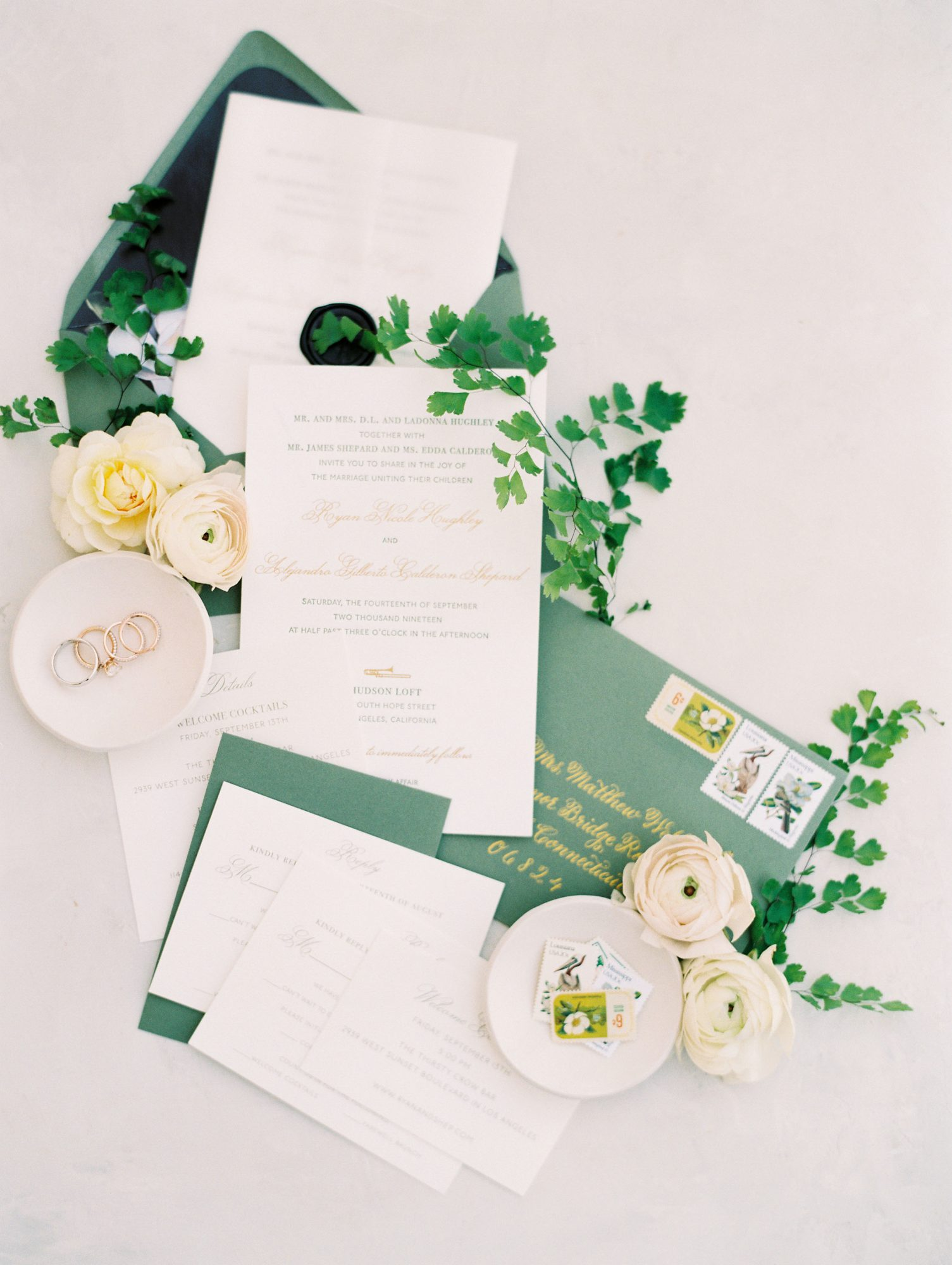 ryan shep wedding invitations surrounded by jewelry and floral decor
