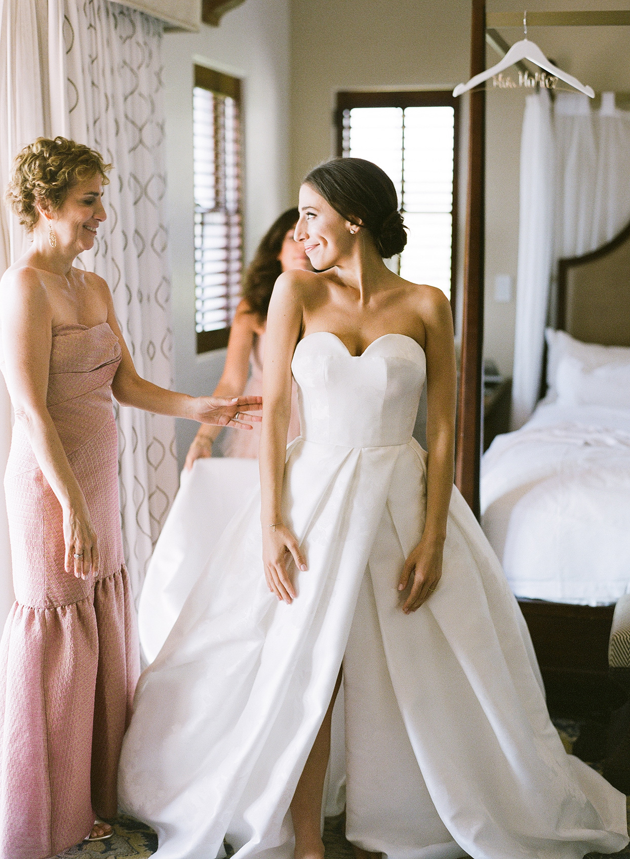bride in white dress with mother and bridesmaid