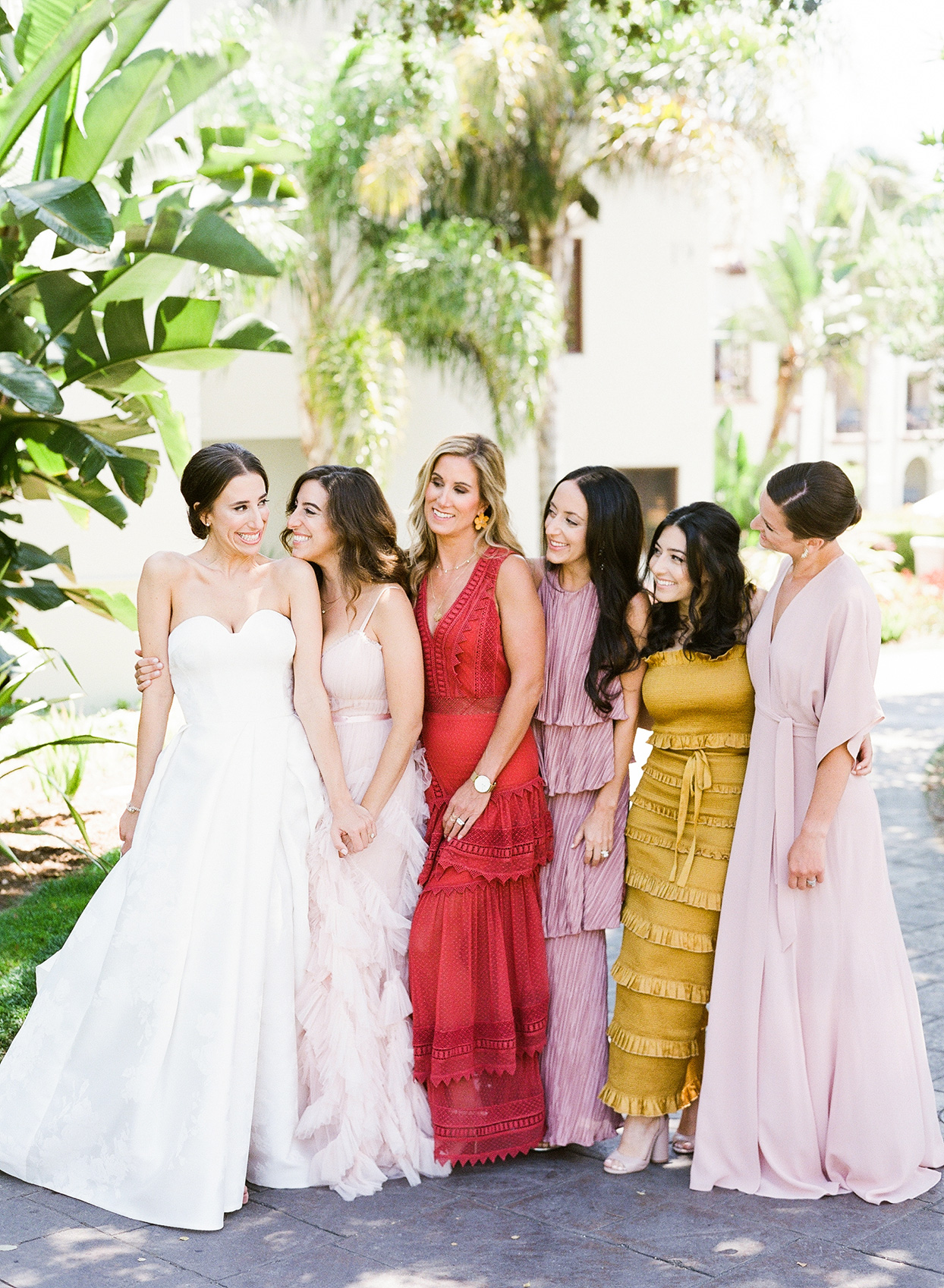 bride with maids in assortment of colored ruffled dresses