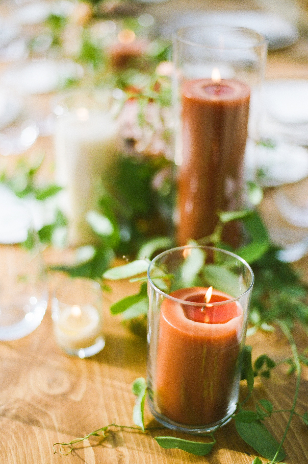burnt orange wedding candles on wooden table with vining greenery