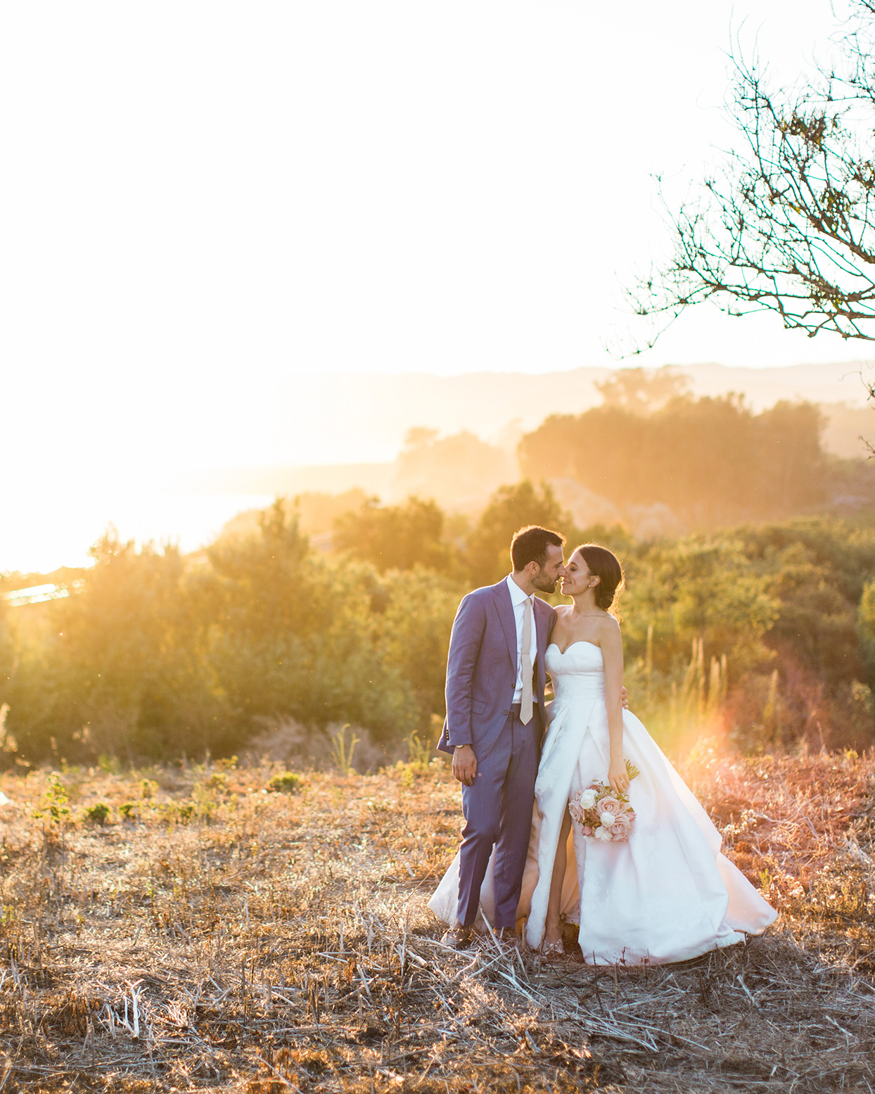wedding couple kissing in field at golden hour