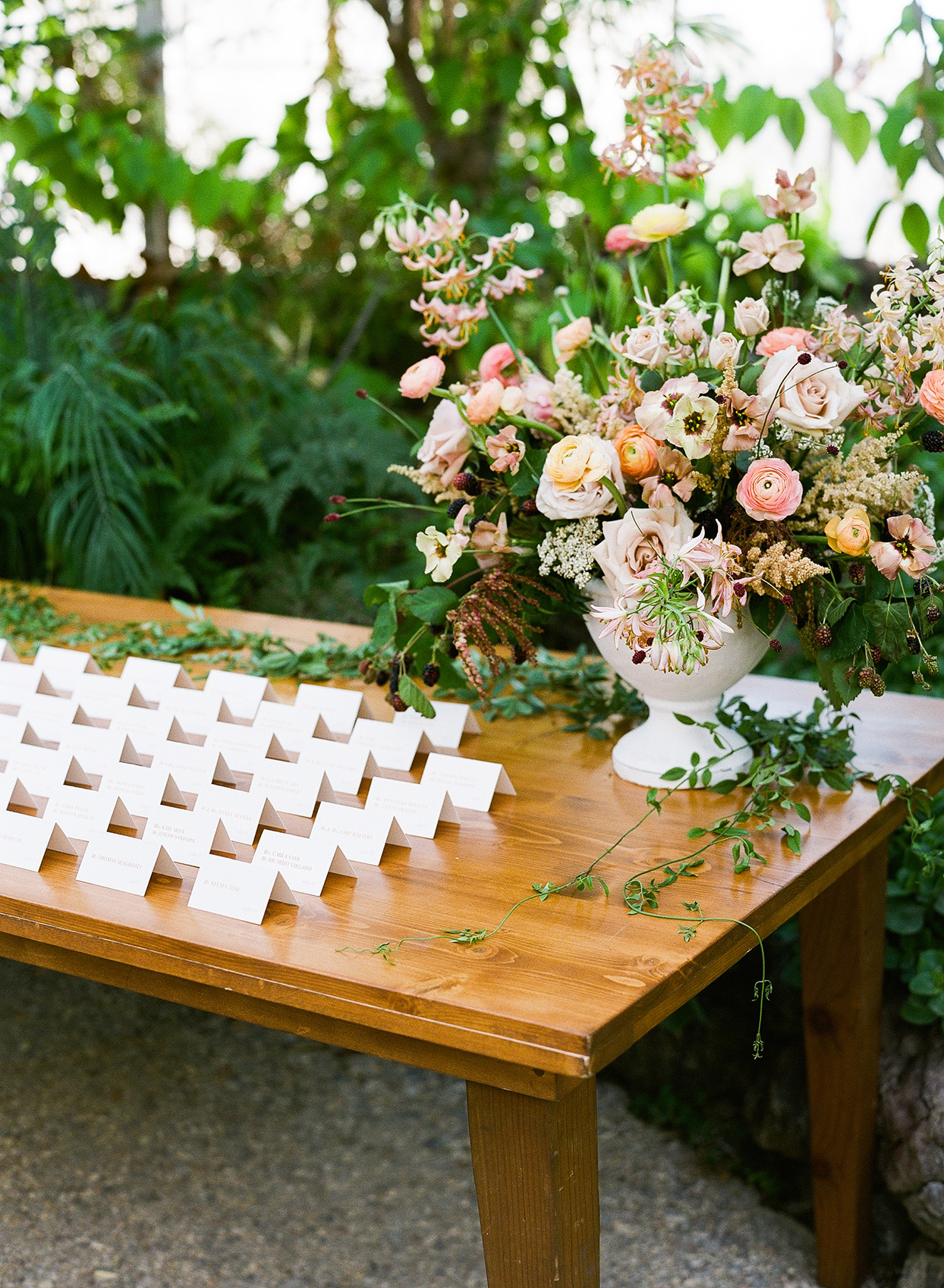 paper escort cards on wooden table with large pot of decorative flowers