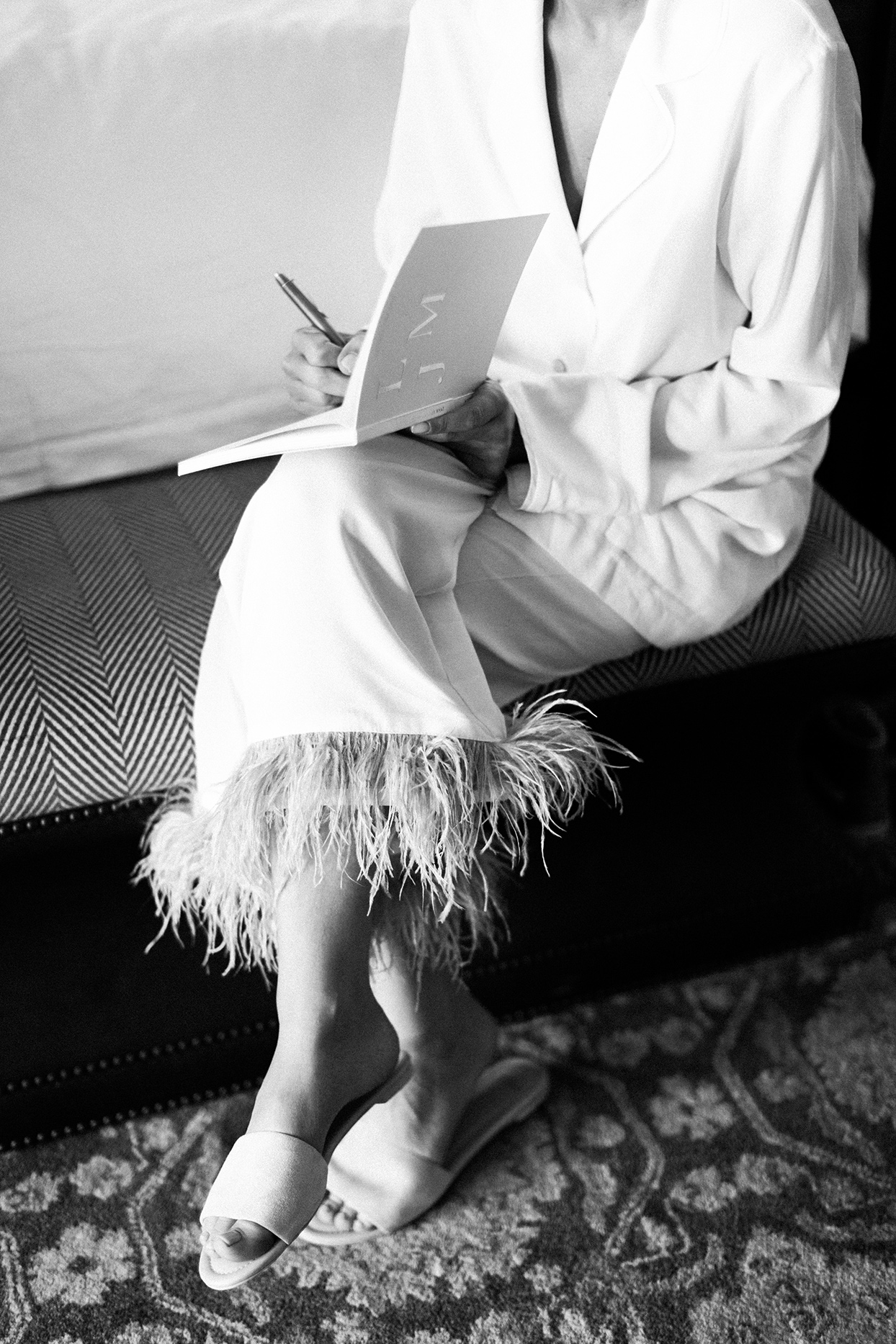 bride sitting in feathered pajamas writing in notebook