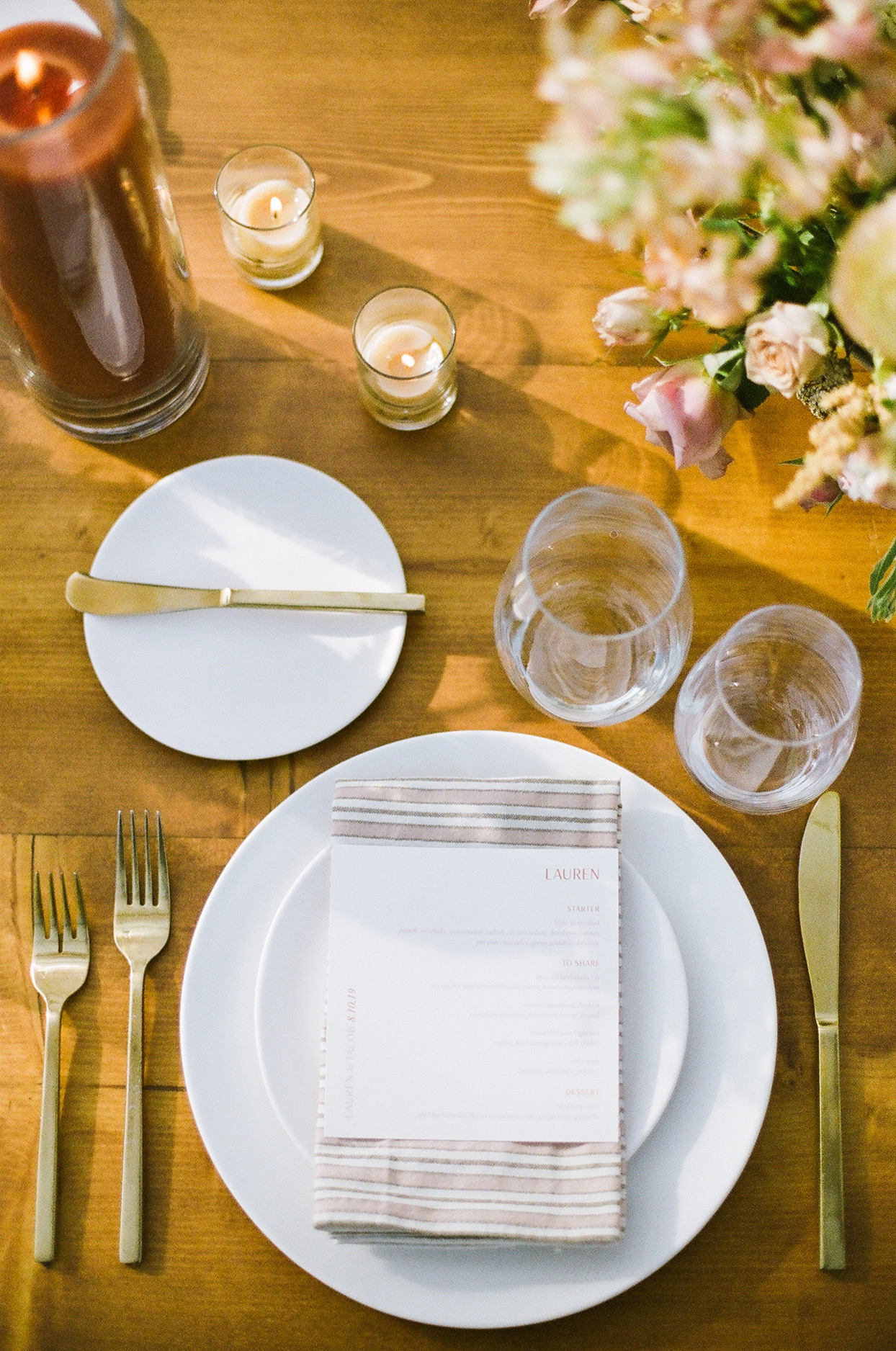 elegant wedding place setting with striped mauve napkins and gold silverware