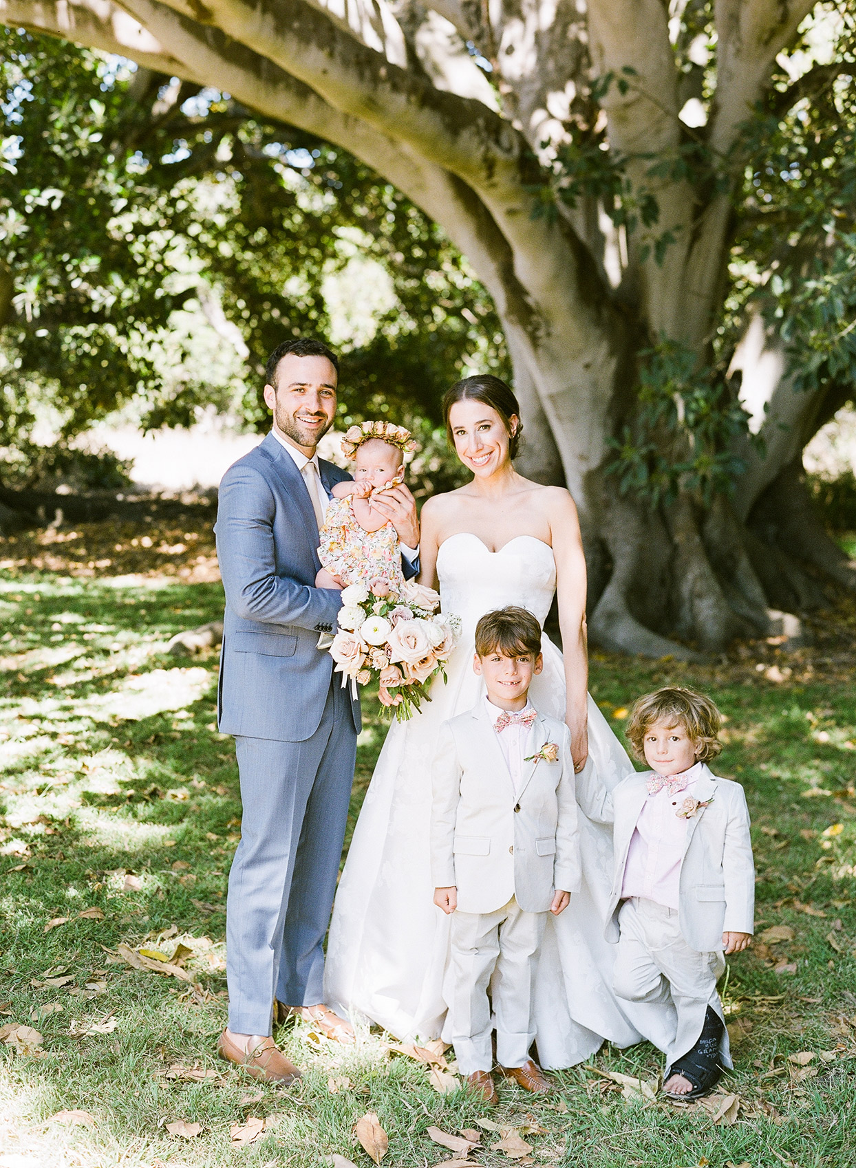 wedding couple with ring bearers under tree