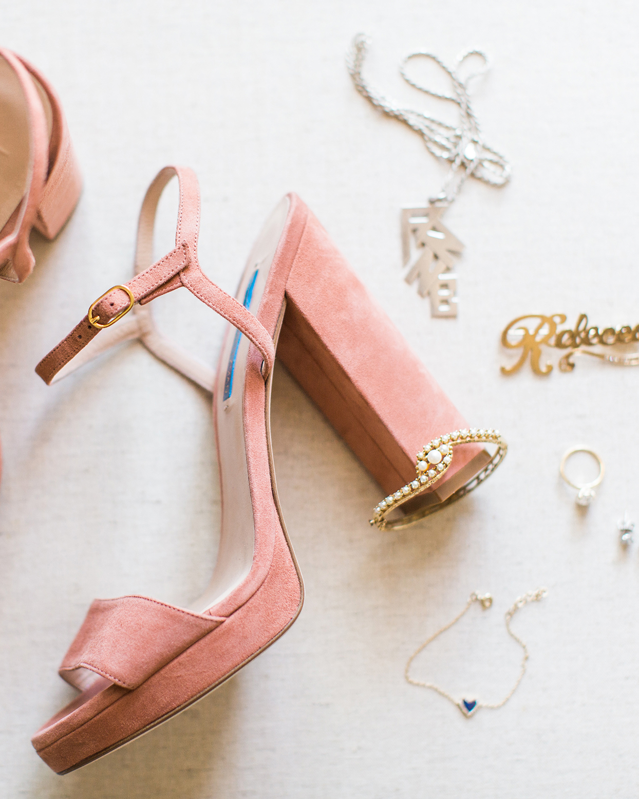 muted coral bride's wedding shoes with pearl bracelet