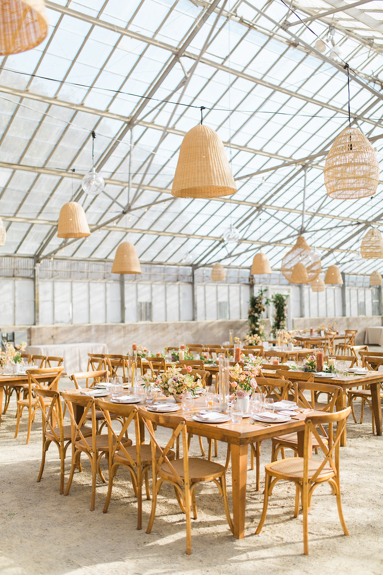 light wood wedding reception tables in industrial greenhouse