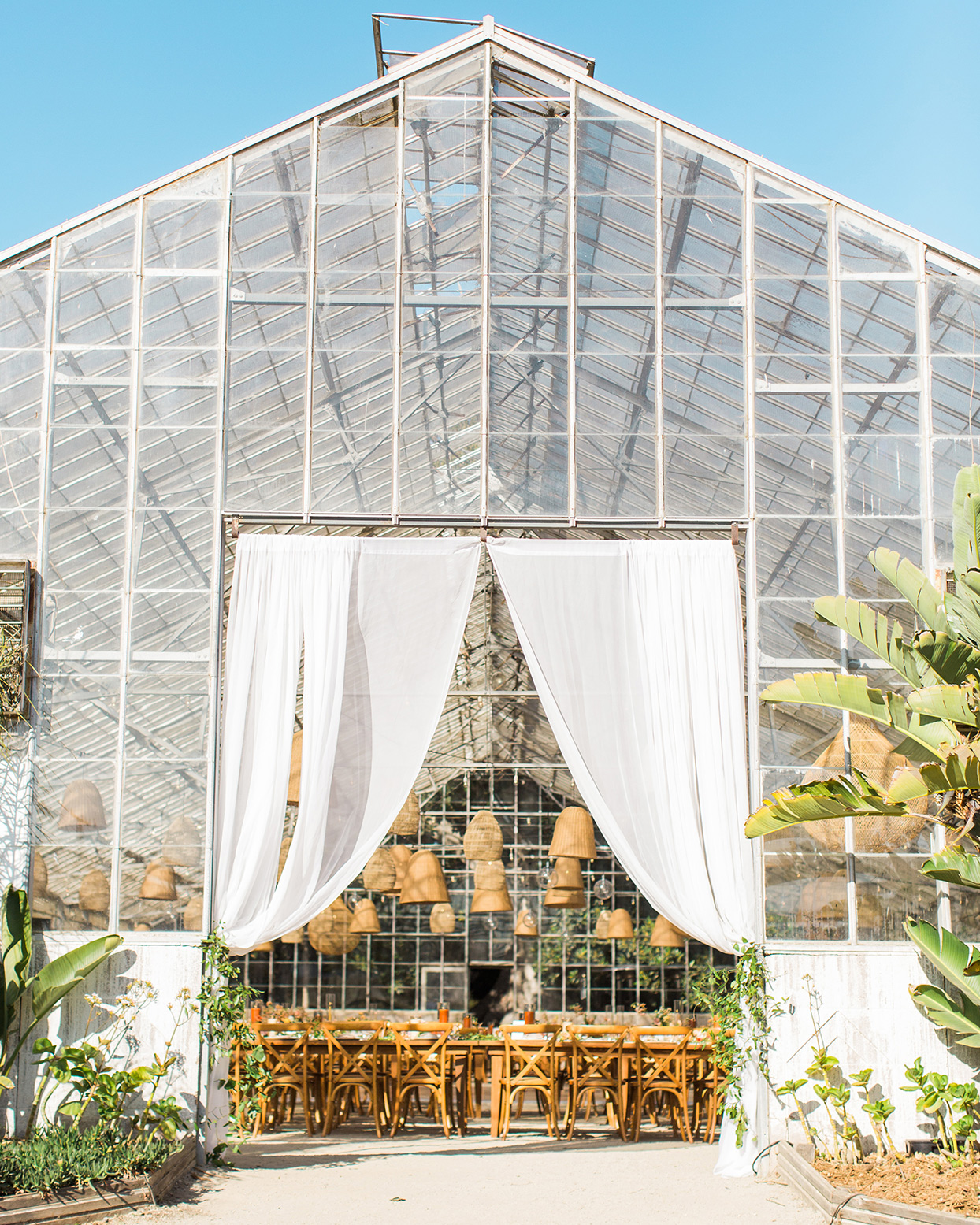 industrial greenhouse wedding venue with reception tables set up inside