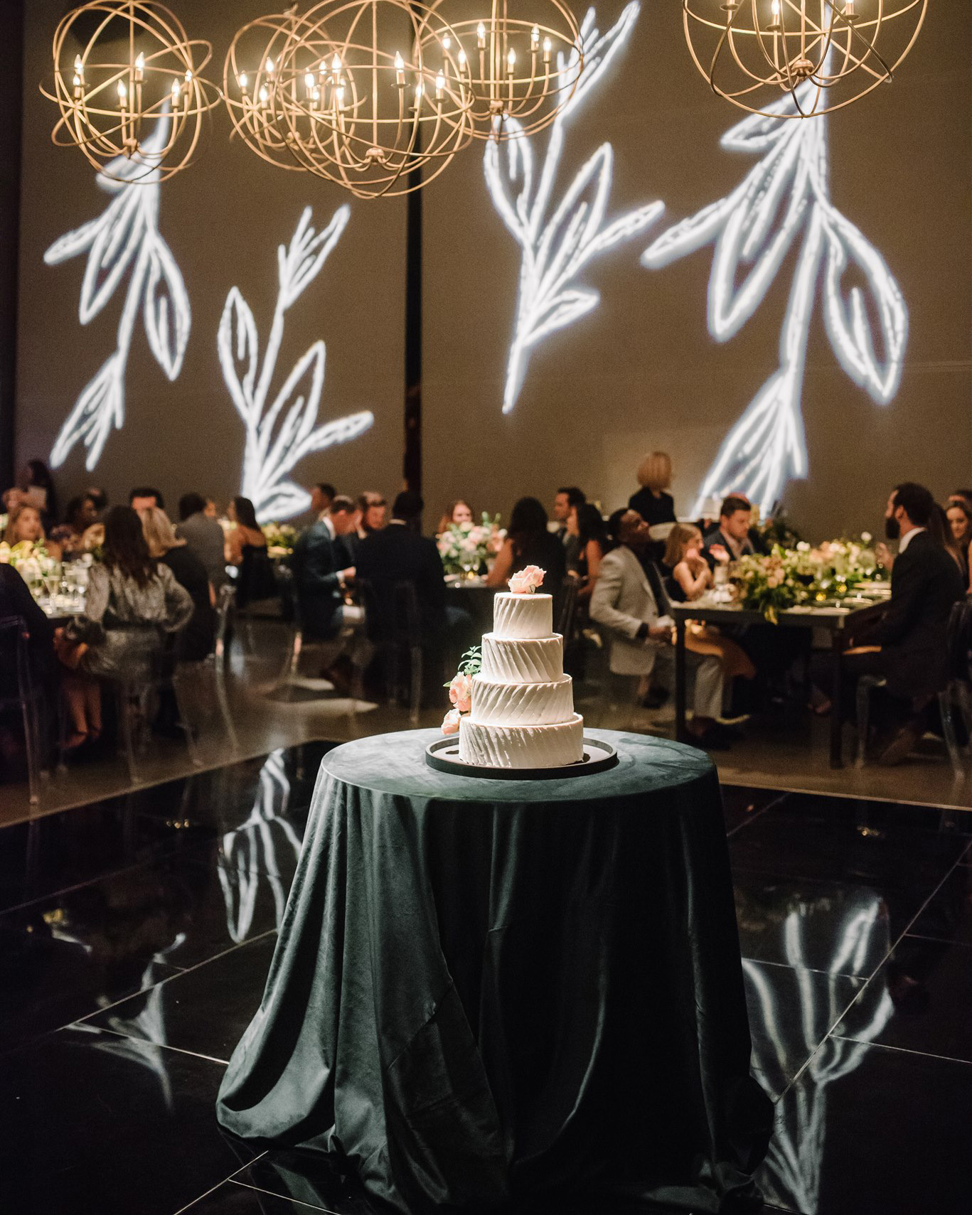 4-tiered white wedding cake guests seated in background