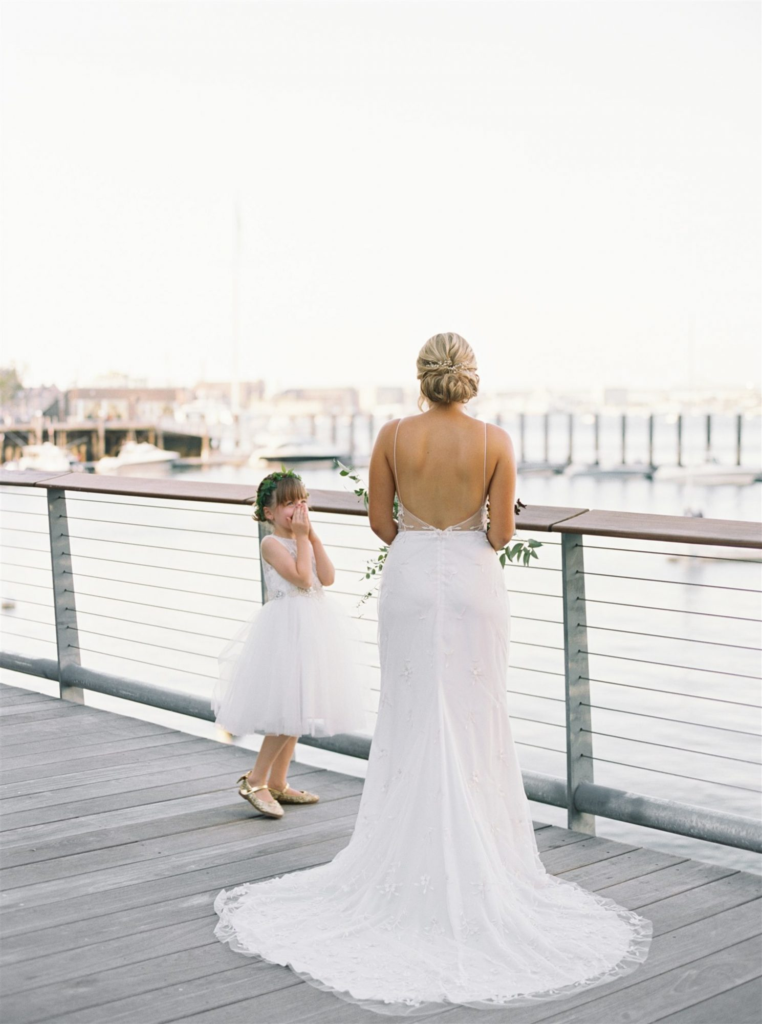 flower girl and bride on deck looking out over water