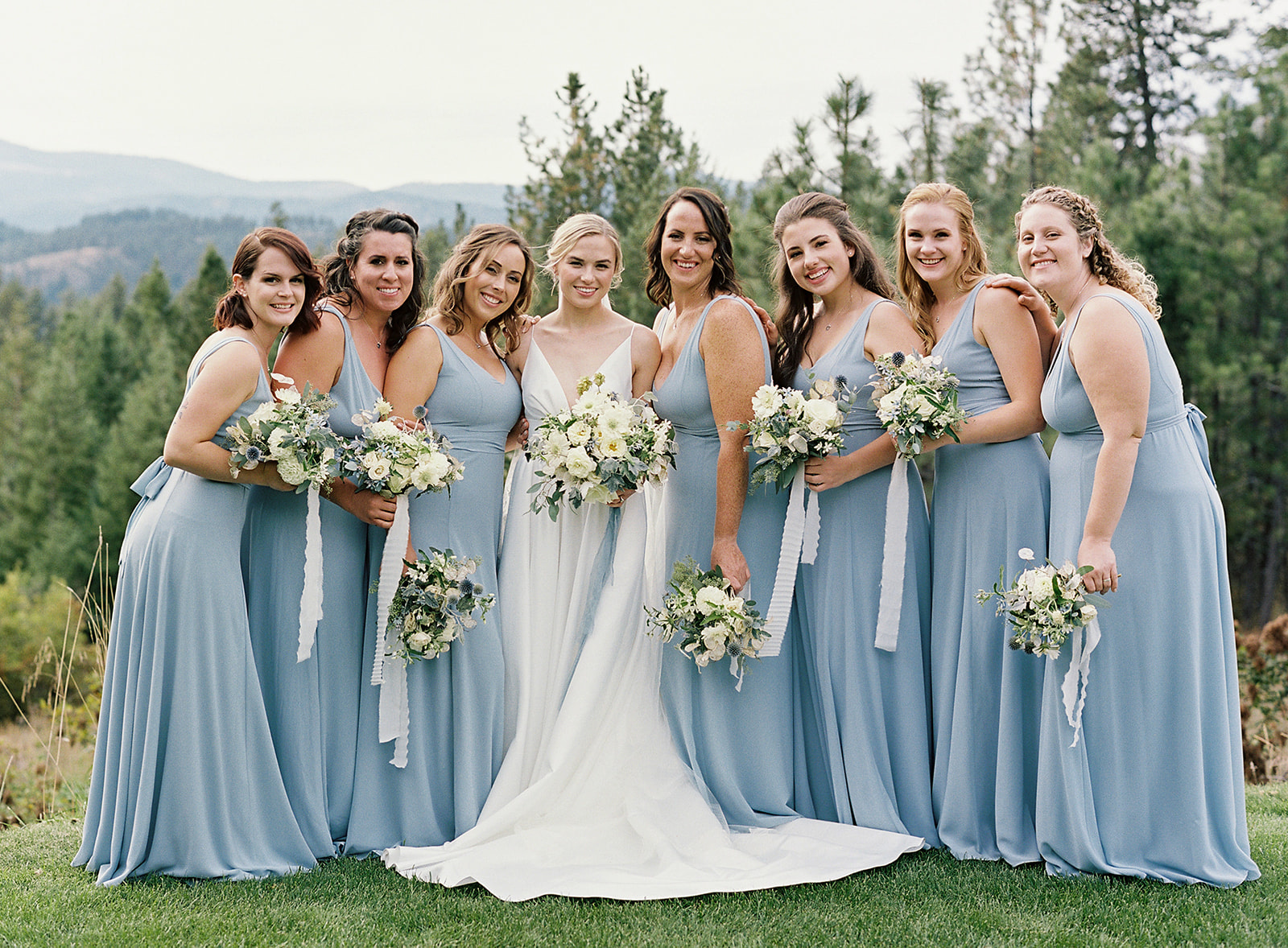 bride surrounded by bridesmaids wearing light blue dresses