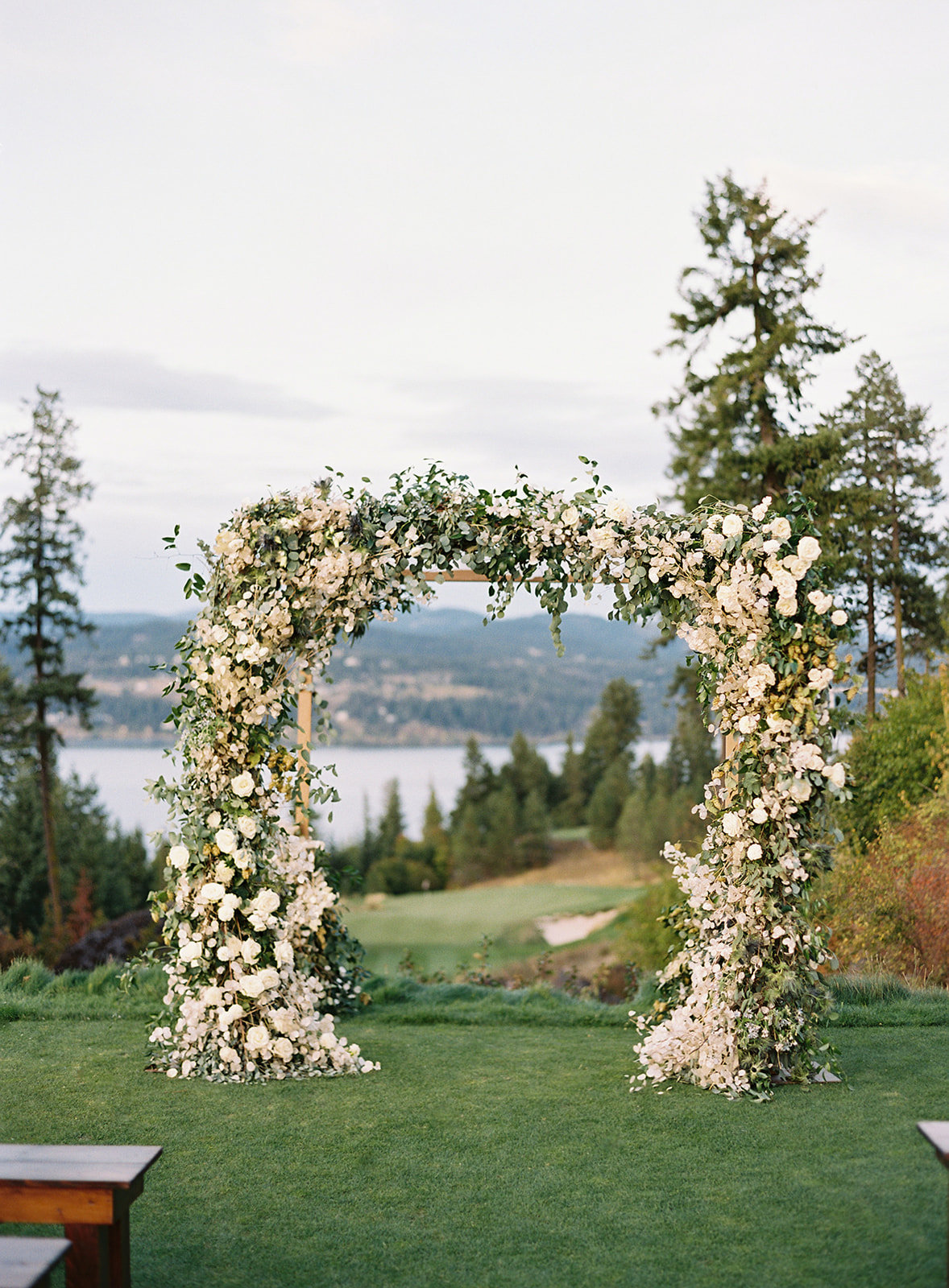 white floral and greenery wedding arch for outside ceremony