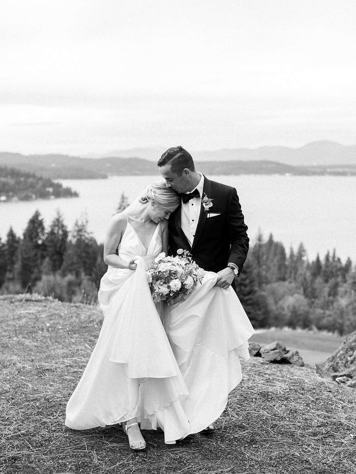 bride and groom embrace outside on hillside