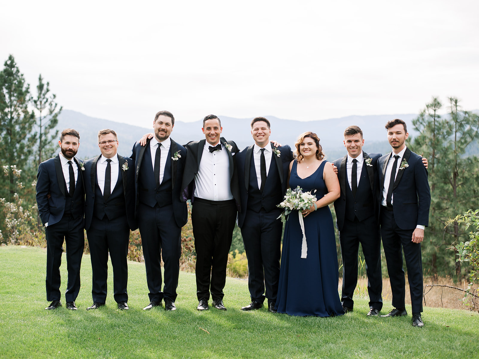 groom standing with groomsmen wearing navy blue suits