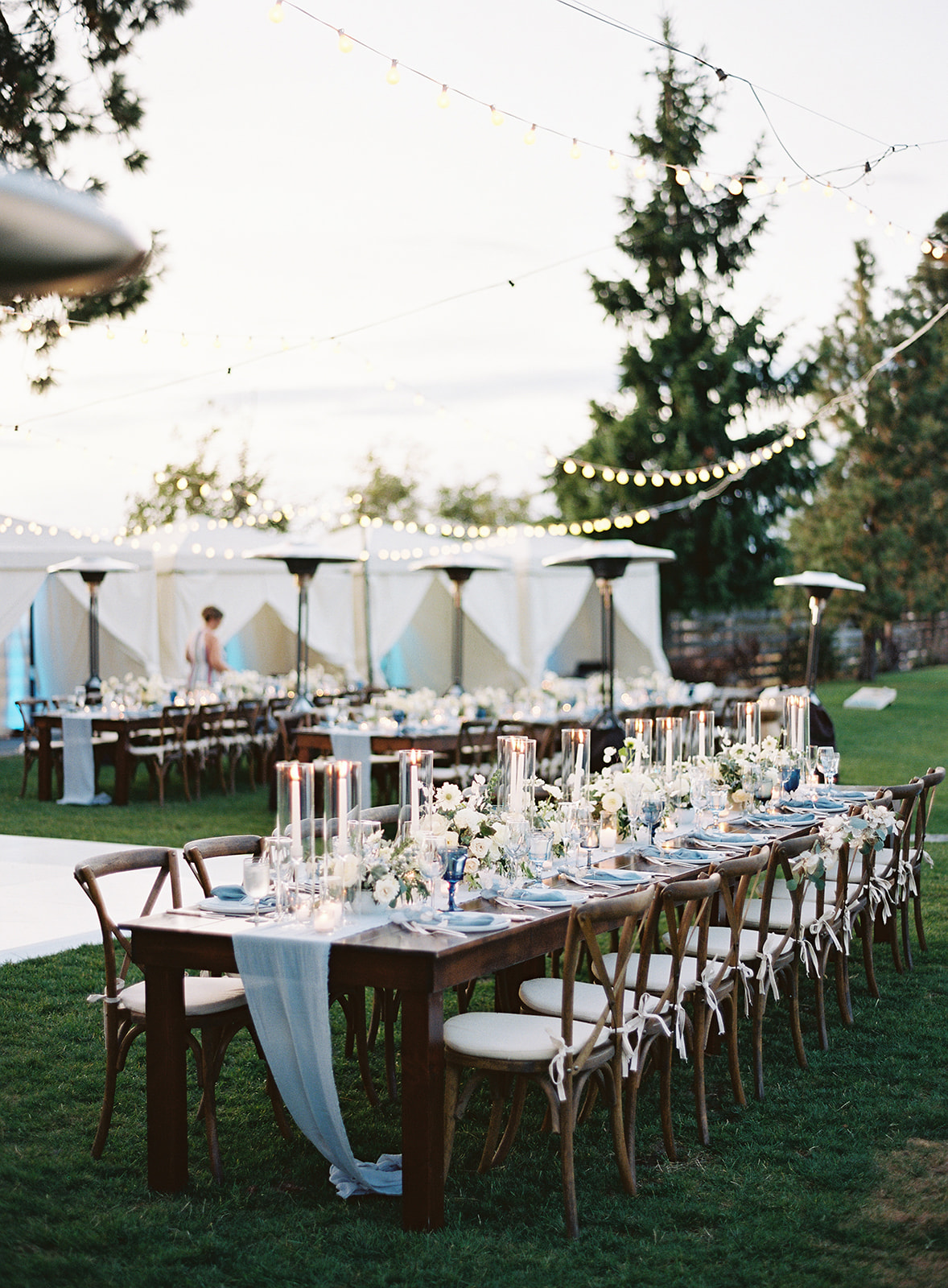 long wooden reception tables outside draped with light blue linens