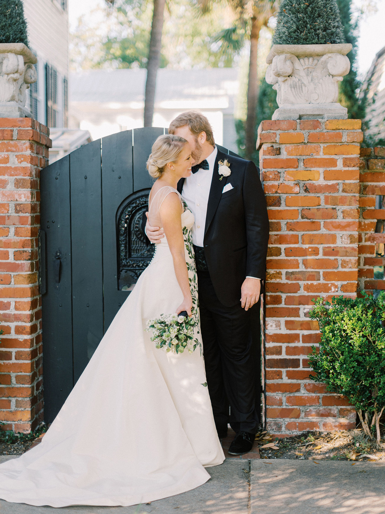 megan parking wedding first look in front of brick wall and black gate