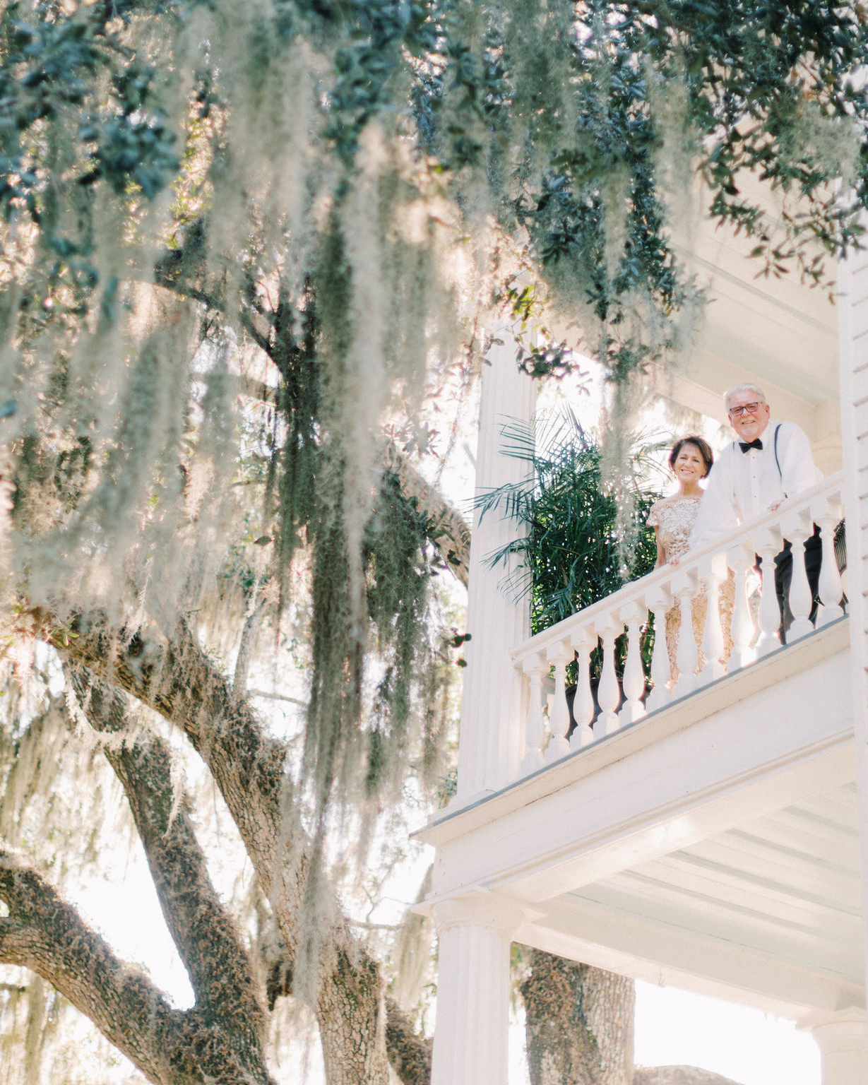 megan parking wedding step parents looking down from white balcony