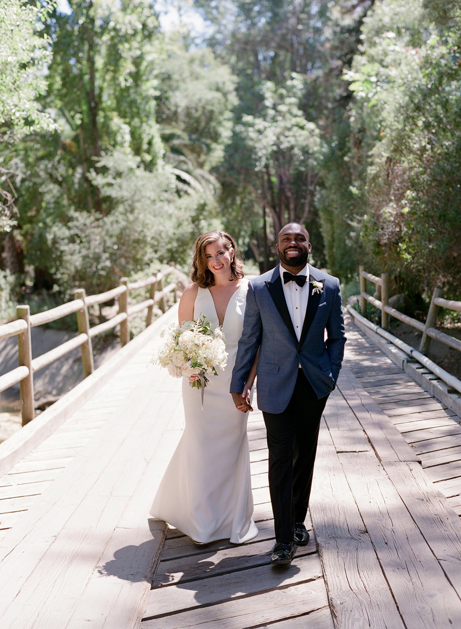 bride and groom holding hands smiling walking over outdoor bridge
