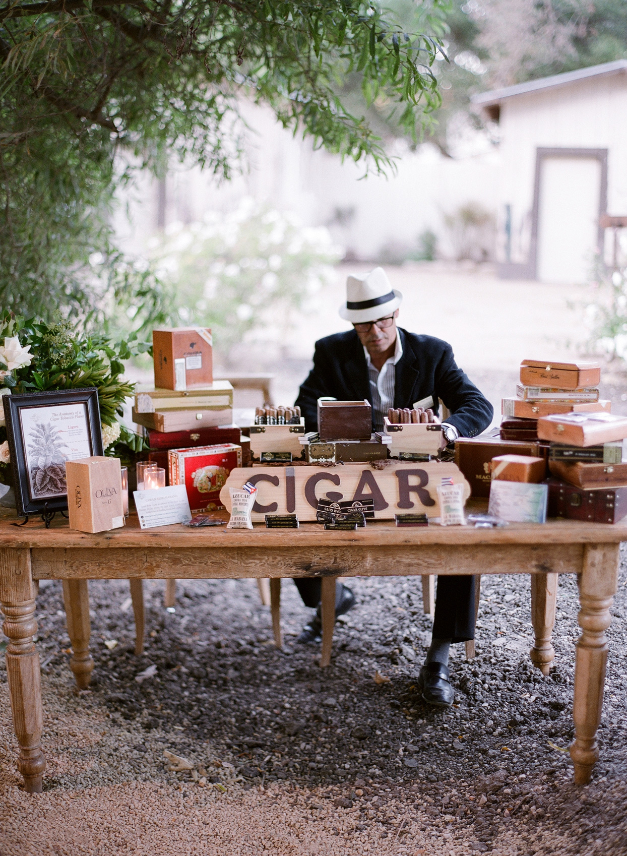 man sitting behind wooden table at reception for cigar booth