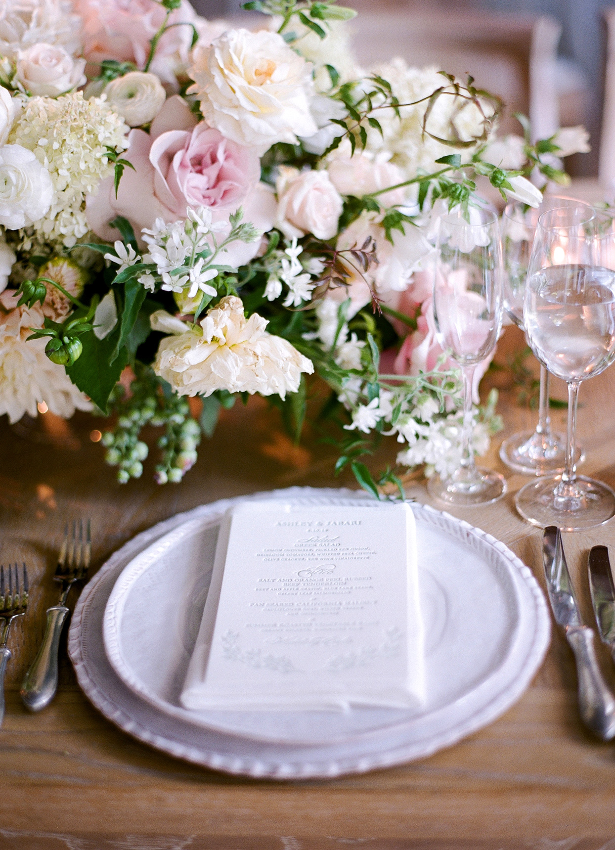 layered white plates with menu and white linen napkins reception place setting