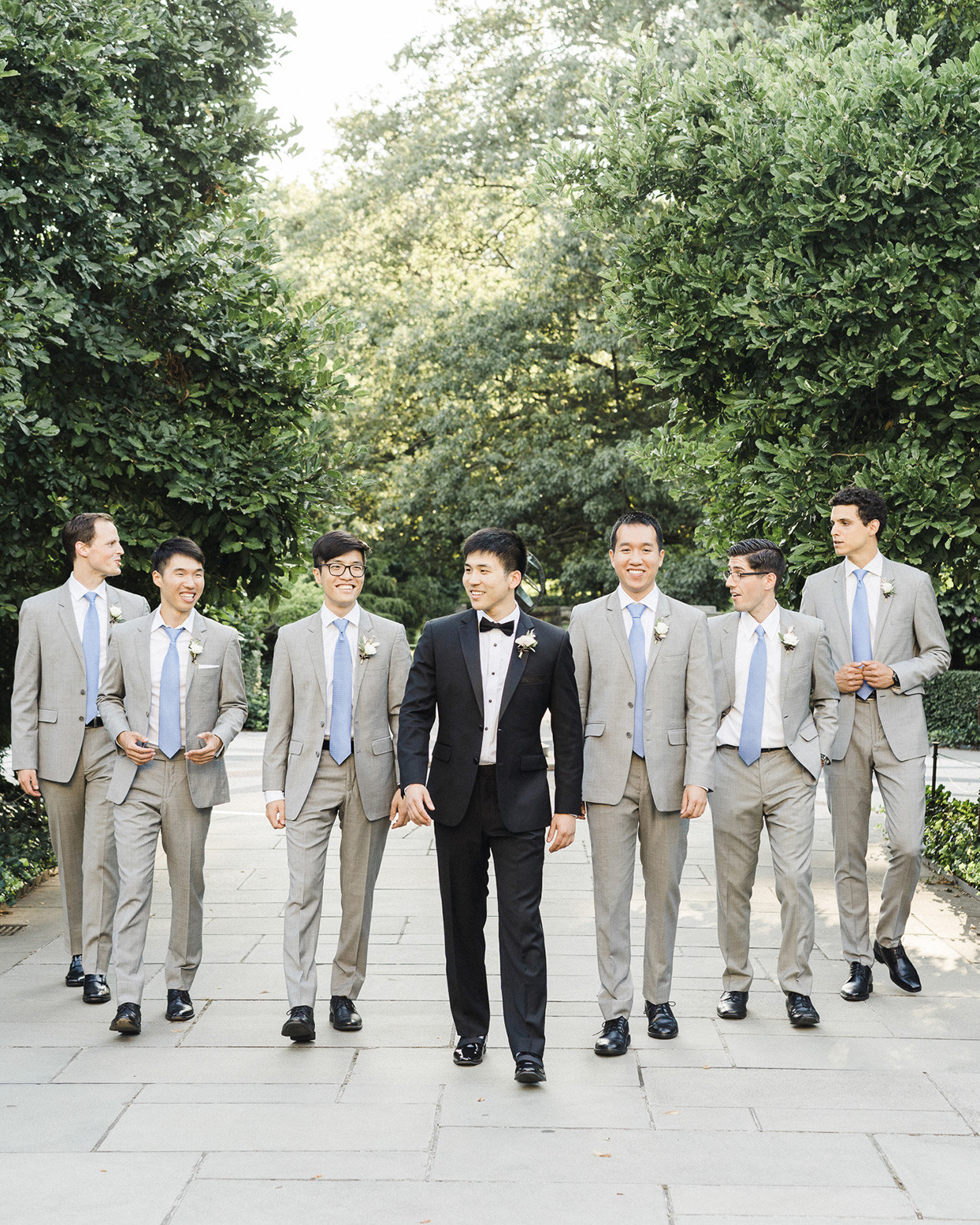 grace john wedding groomsmen in gray and blue walking with groom in black