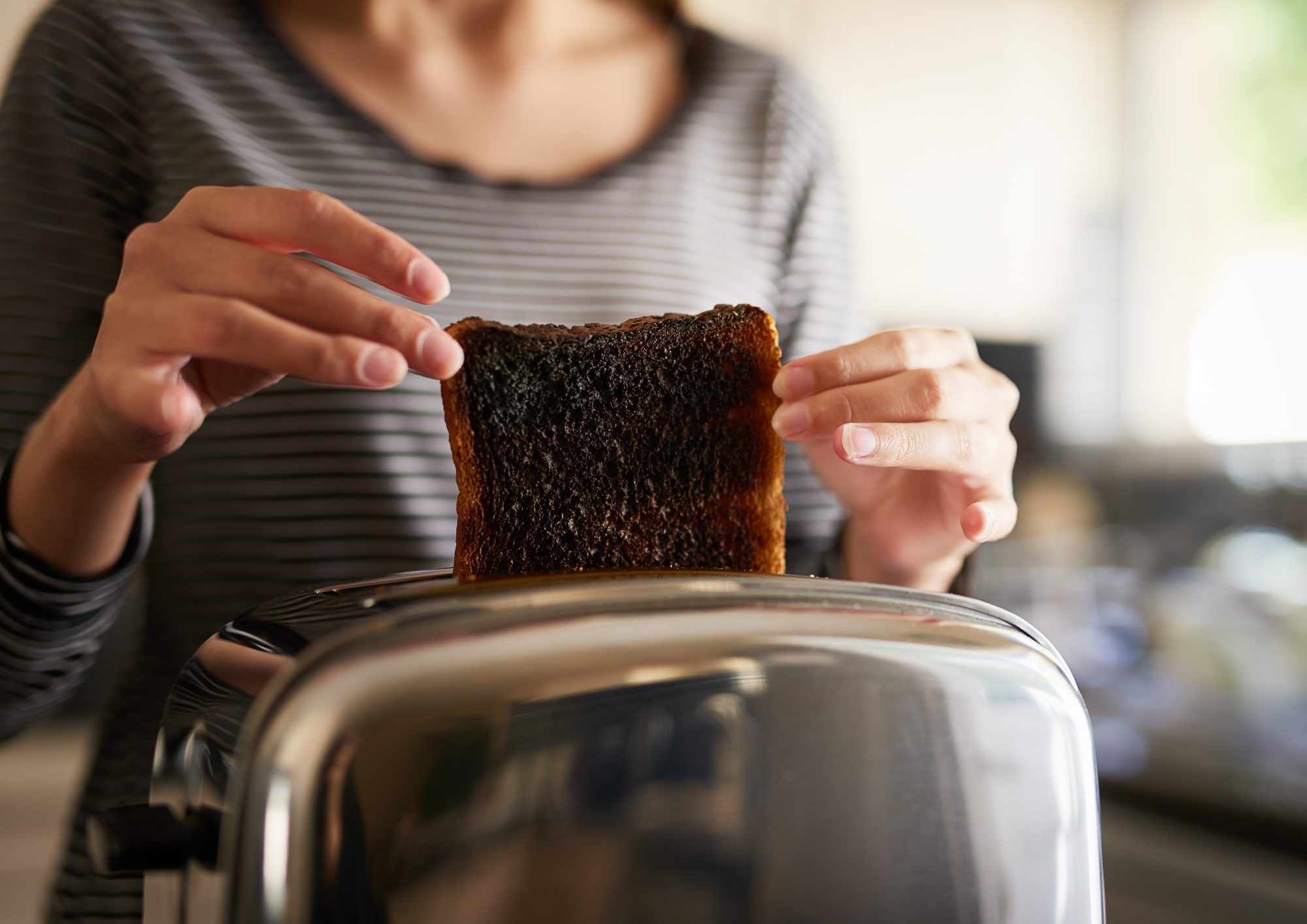 woman removing burned toast from a toaster