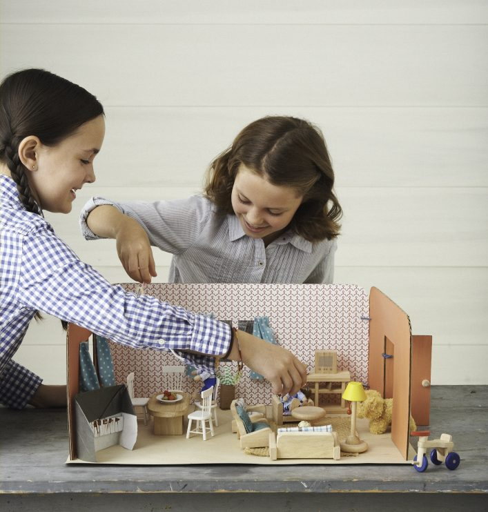 two little girls playing with a cardboard dollhouse