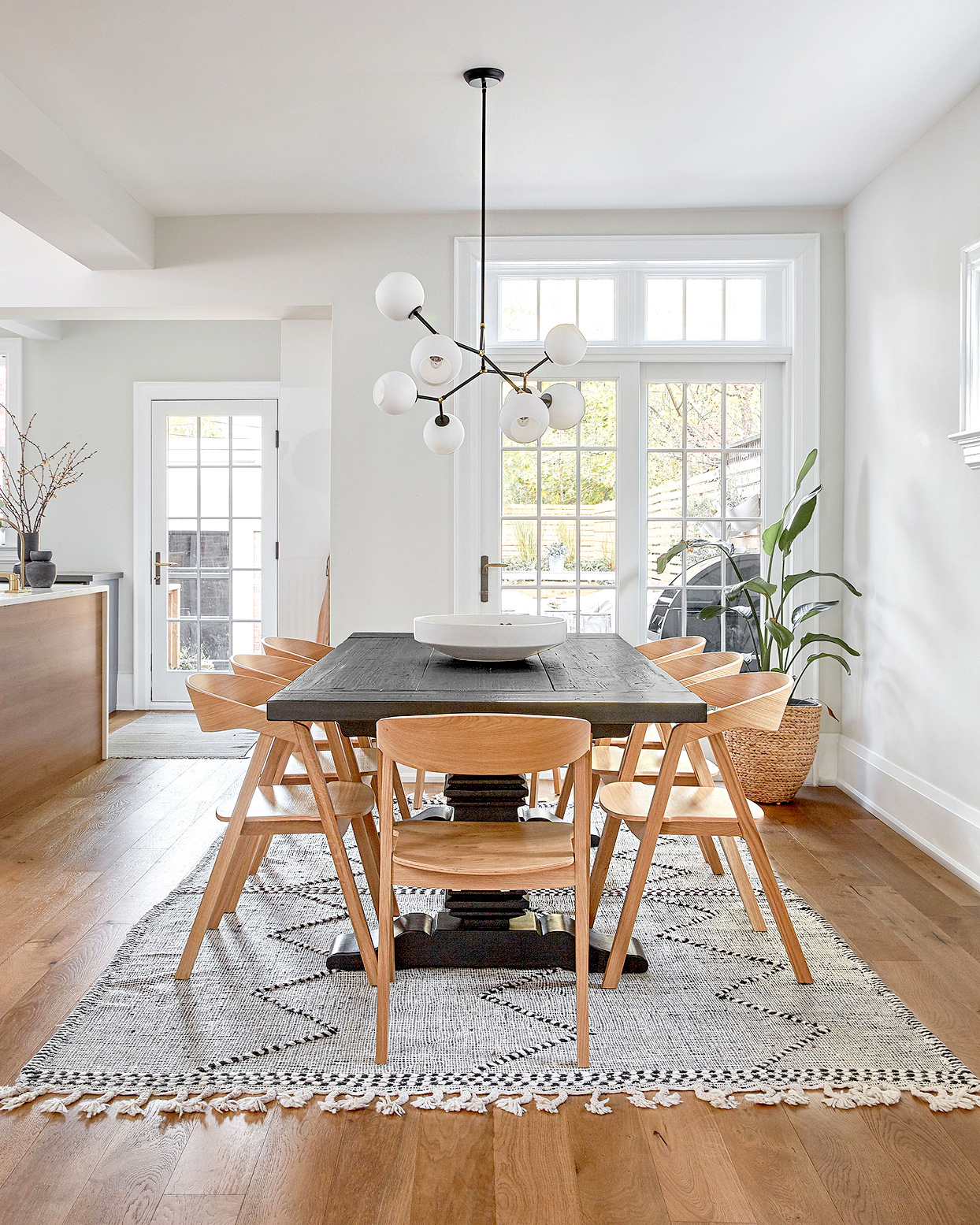 Dining area with large woven rug and wooden table and chairs