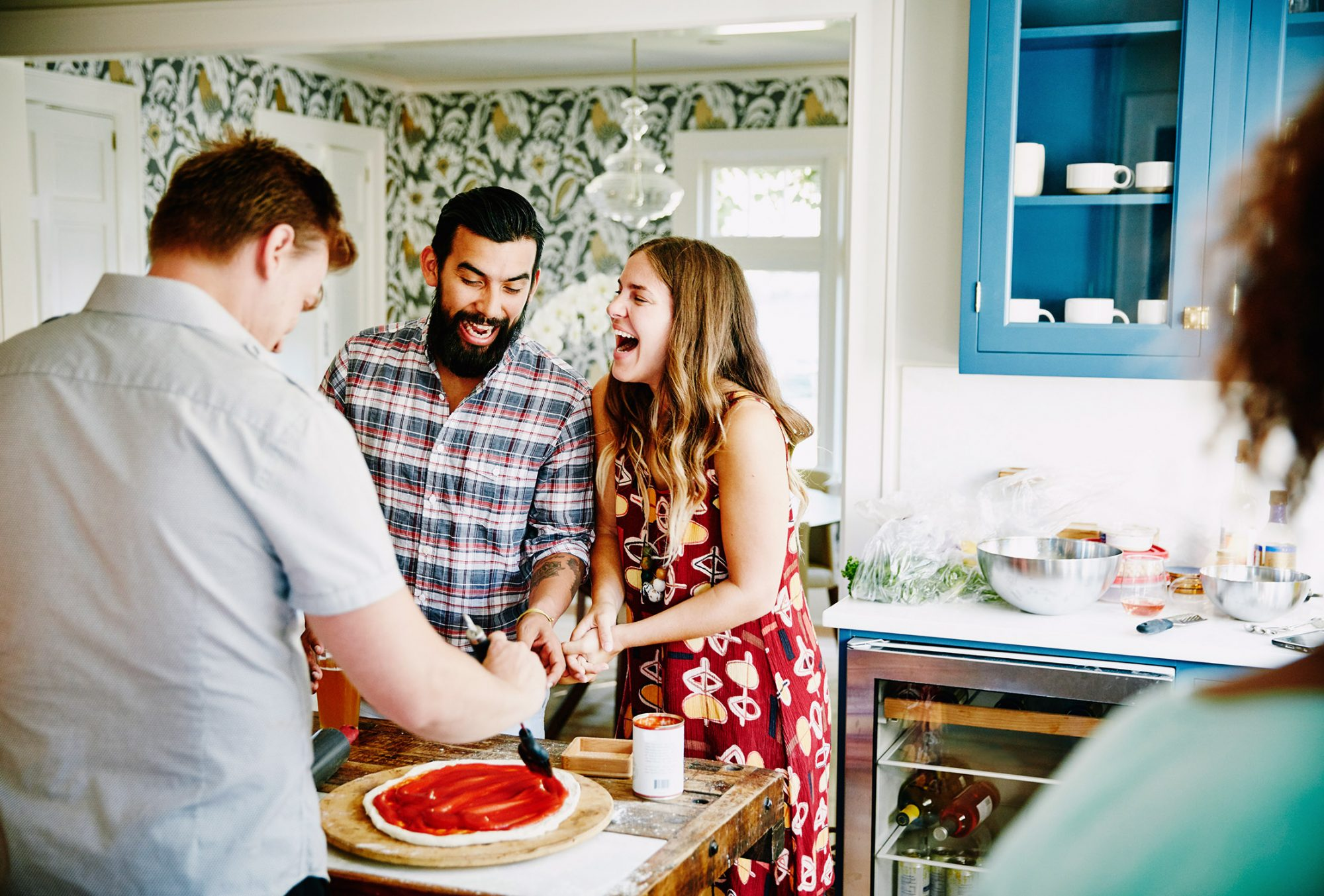 Laughing couple preparing pizza together with friends in kitchen