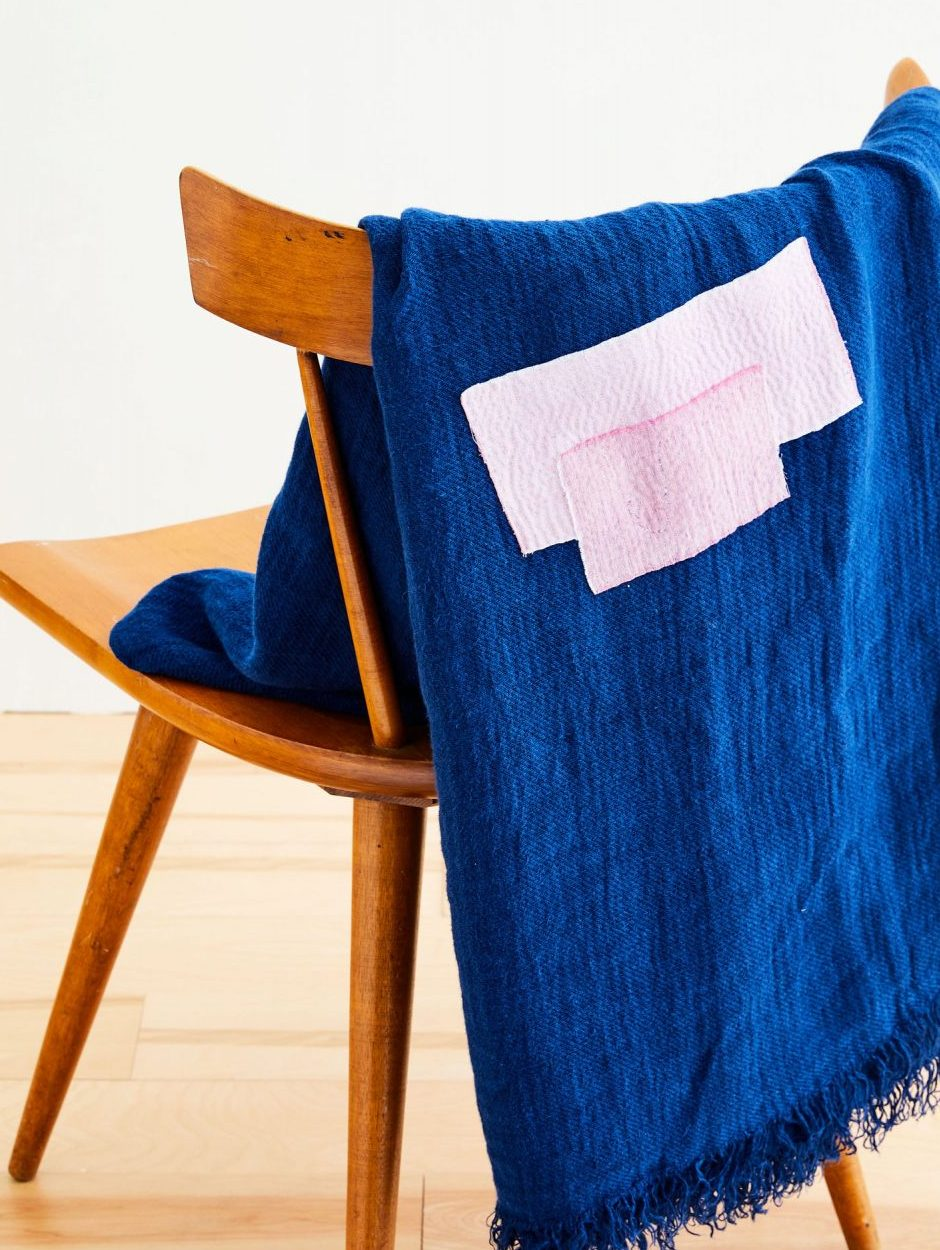 a mended blanket draped over a chair