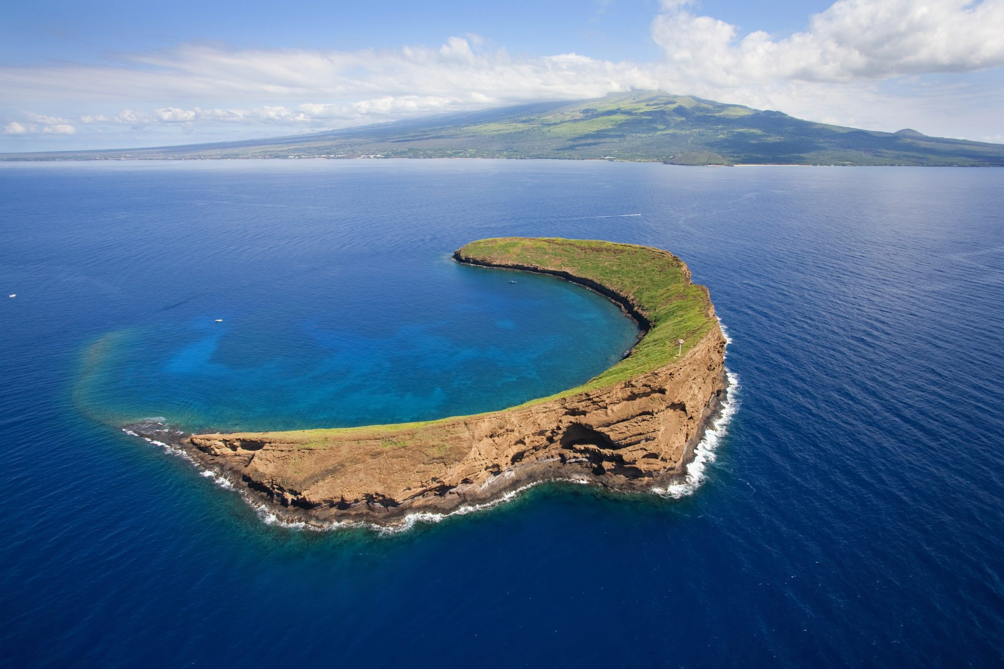Molokini islet, famous snorkeling location off the coast of Maui, Hawaii. Molokini is a marine preserve protected by the State of Hawaii. Maui is in the background.