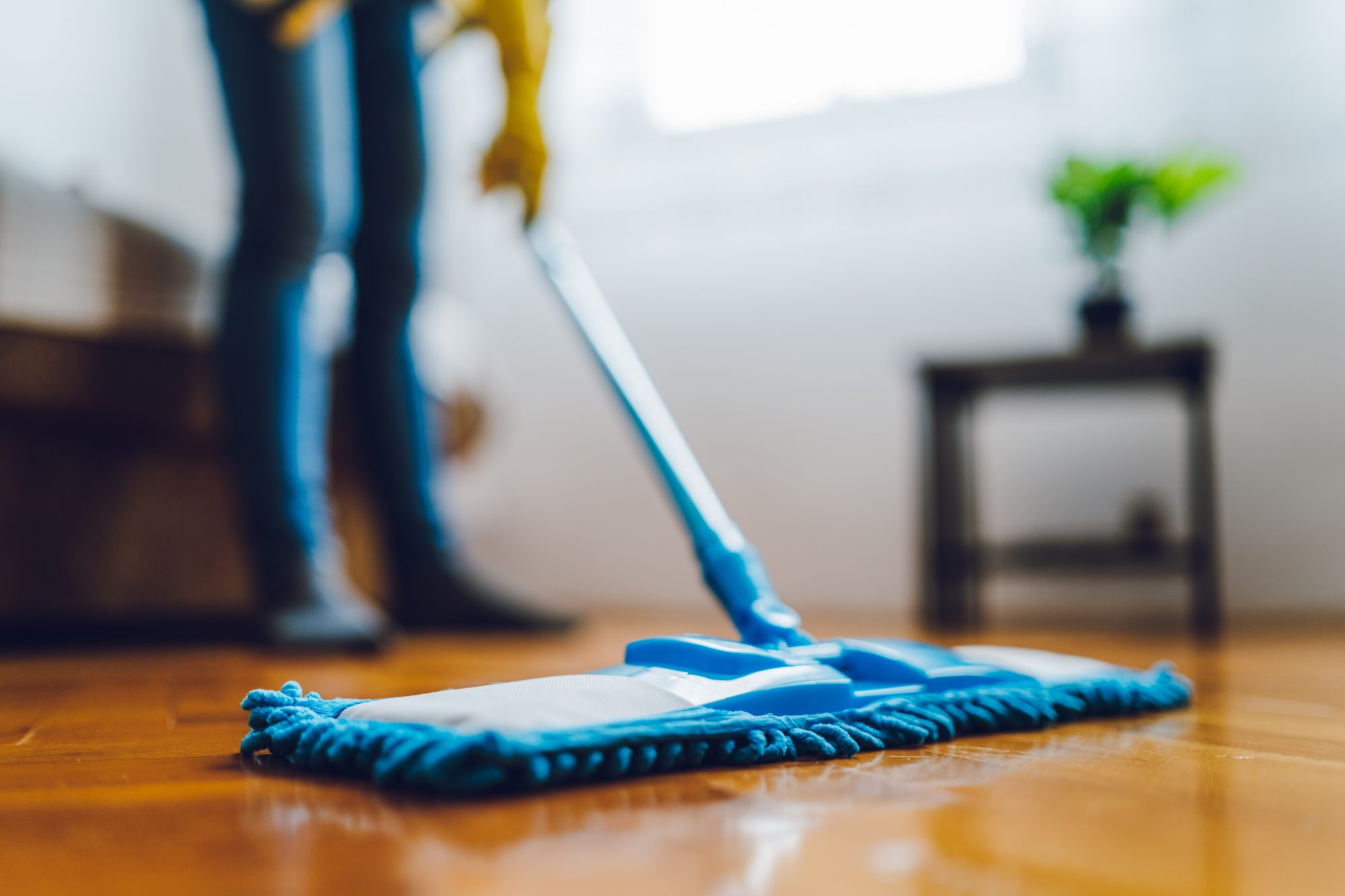 woman mopping with blue mop