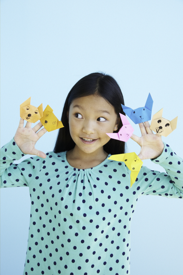 little girl holding up her origami finger puppets