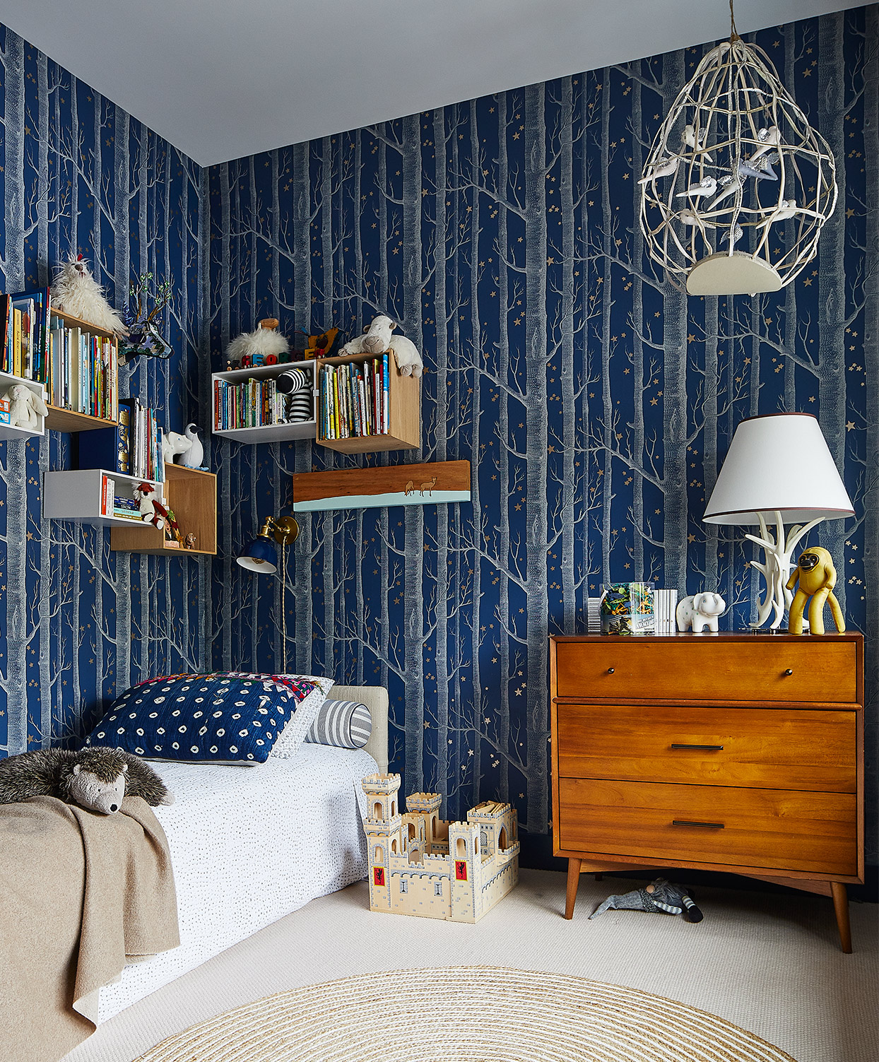 blue kid's bedroom with tree patterned walls and floating shelves