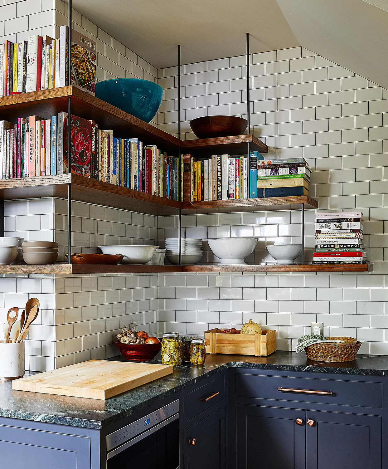 kitchen corner with blue cabinets and hanging exposed shelves with cookbooks and dishes